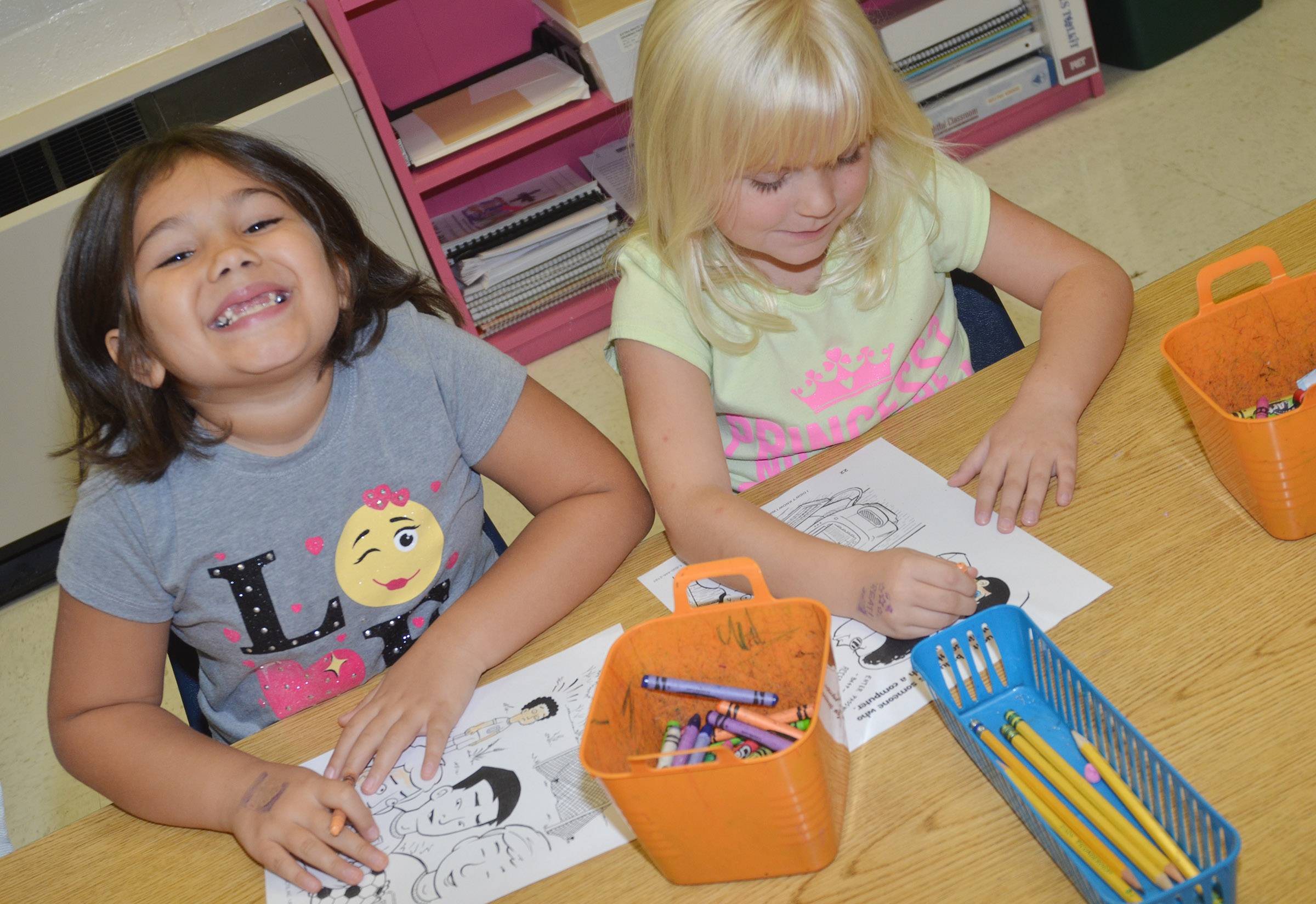 CES first-graders Hannah Matias, at left, and Ava Bennett-Marr color their pages of their class's bullying book.