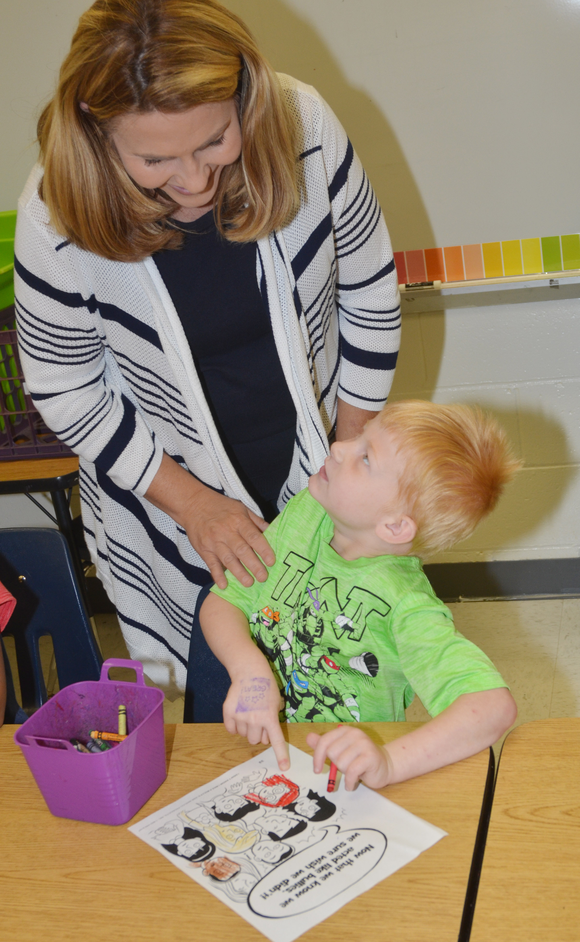 CES Guidance Counselor Sonya Orberson talks to first-grader Jayden Maupin about his page of the class's bullying book.
