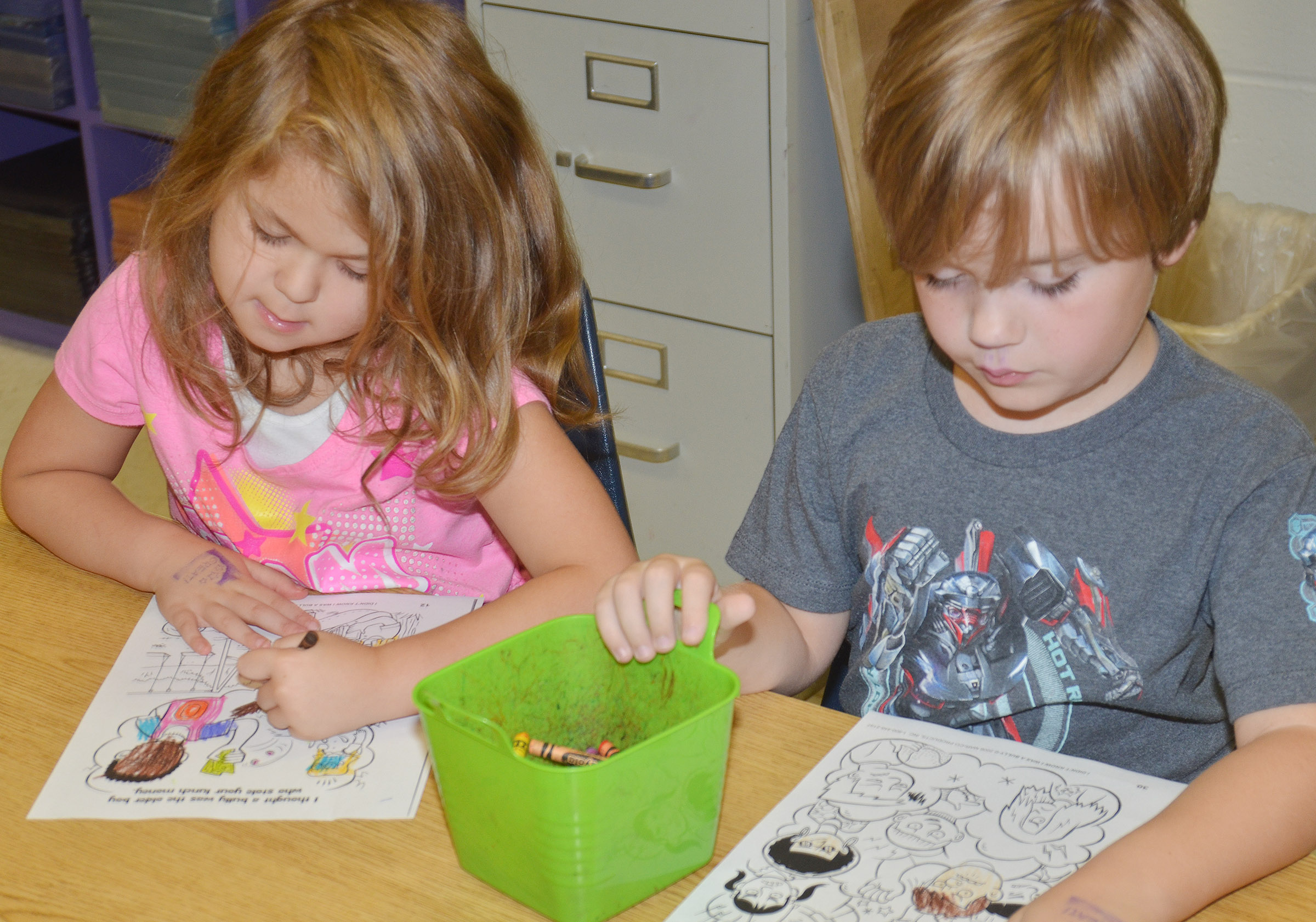 CES first-graders Aubrey Wilson, at left, and Gavin Williams color their pages of their class's bullying book.