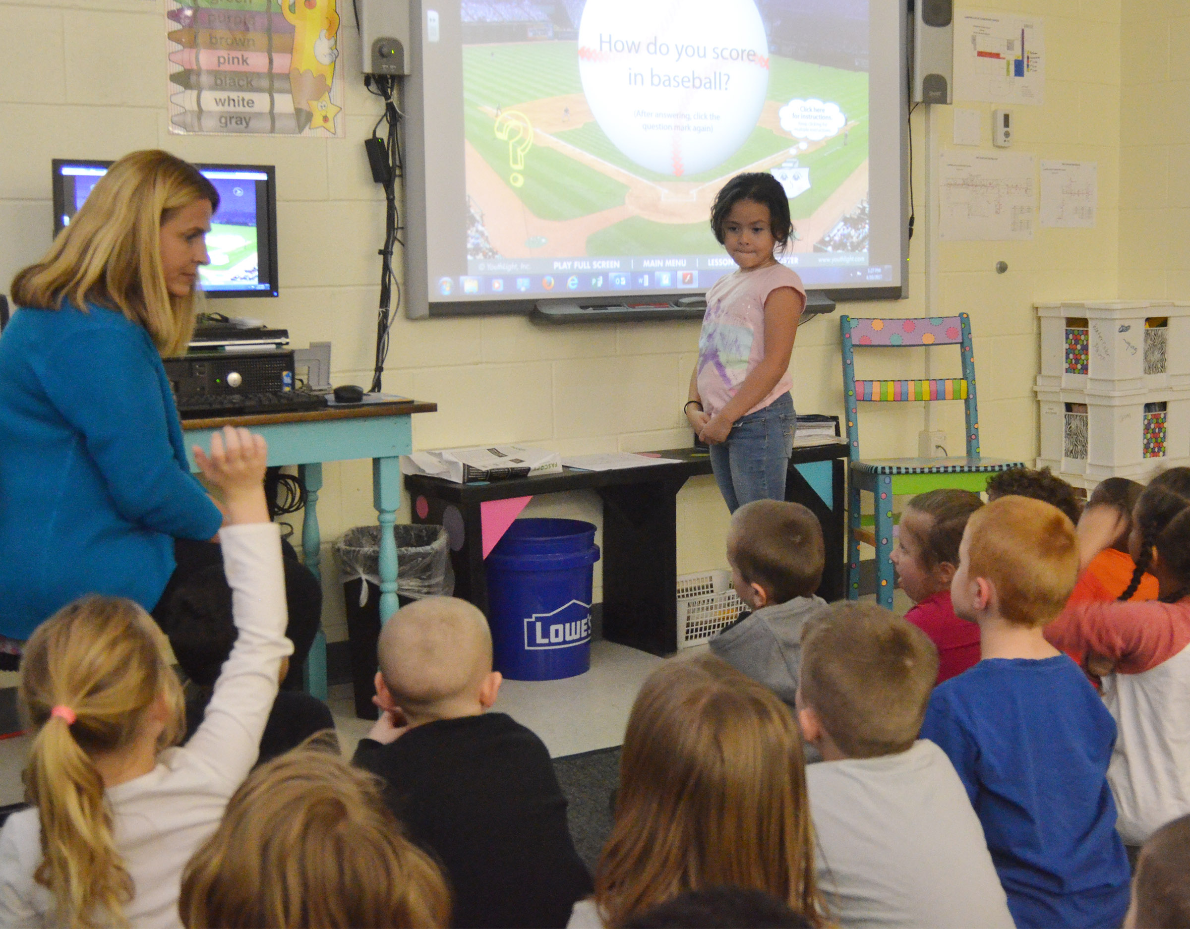 CES kindergartener Isabella Anderson helps Guidance Counselor Sonya Orberson answer a question about a respect. By answering the question correctly, Anderson's baseball team scored a run.