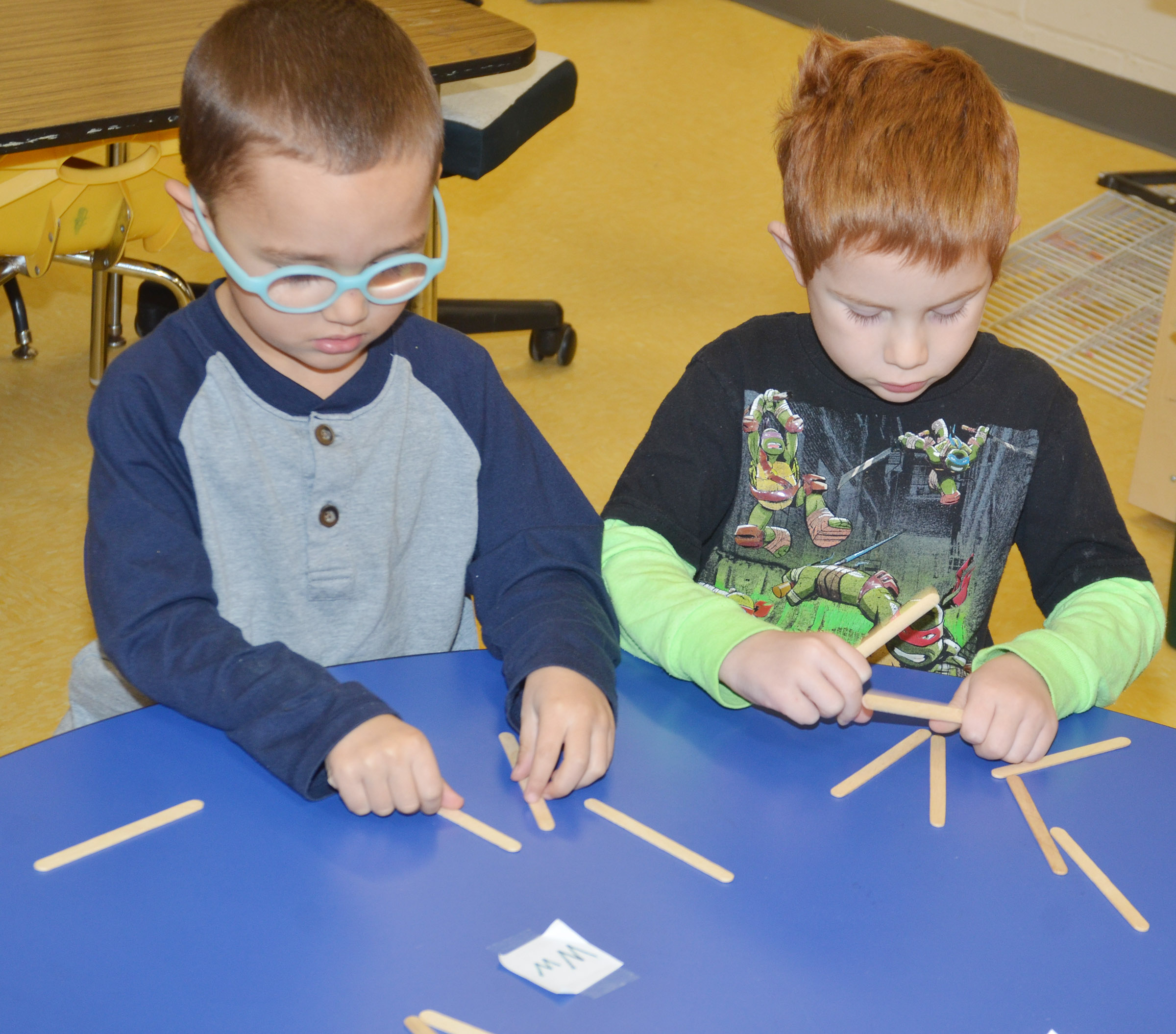 "CES preschool students Chanler Mann, at left, and Kennon Dotson make the letter ""W"" with Popsicle sticks."