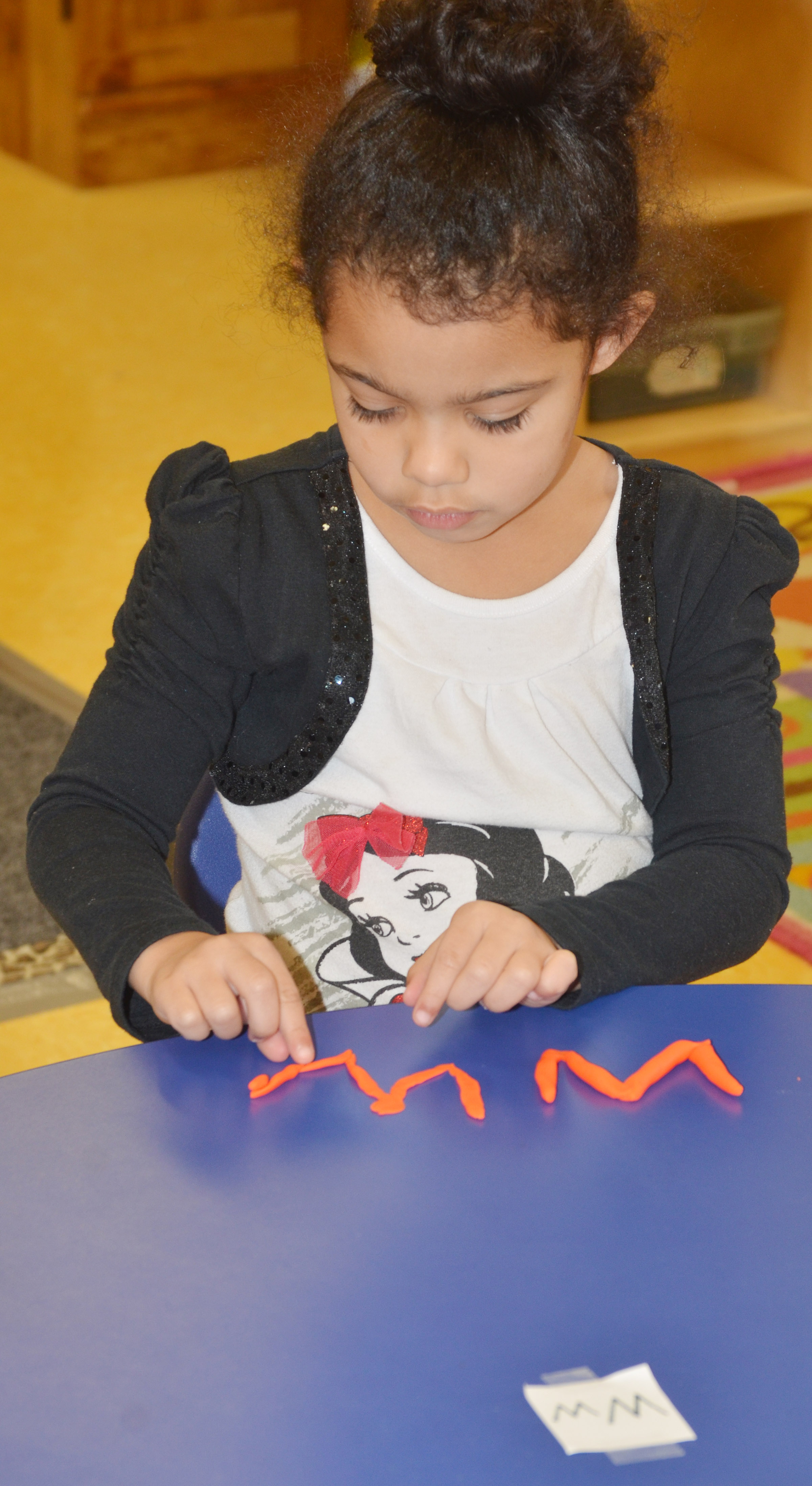 "CES preschool student Rylee Karr makes the letter ""W"" with Play-Doh."