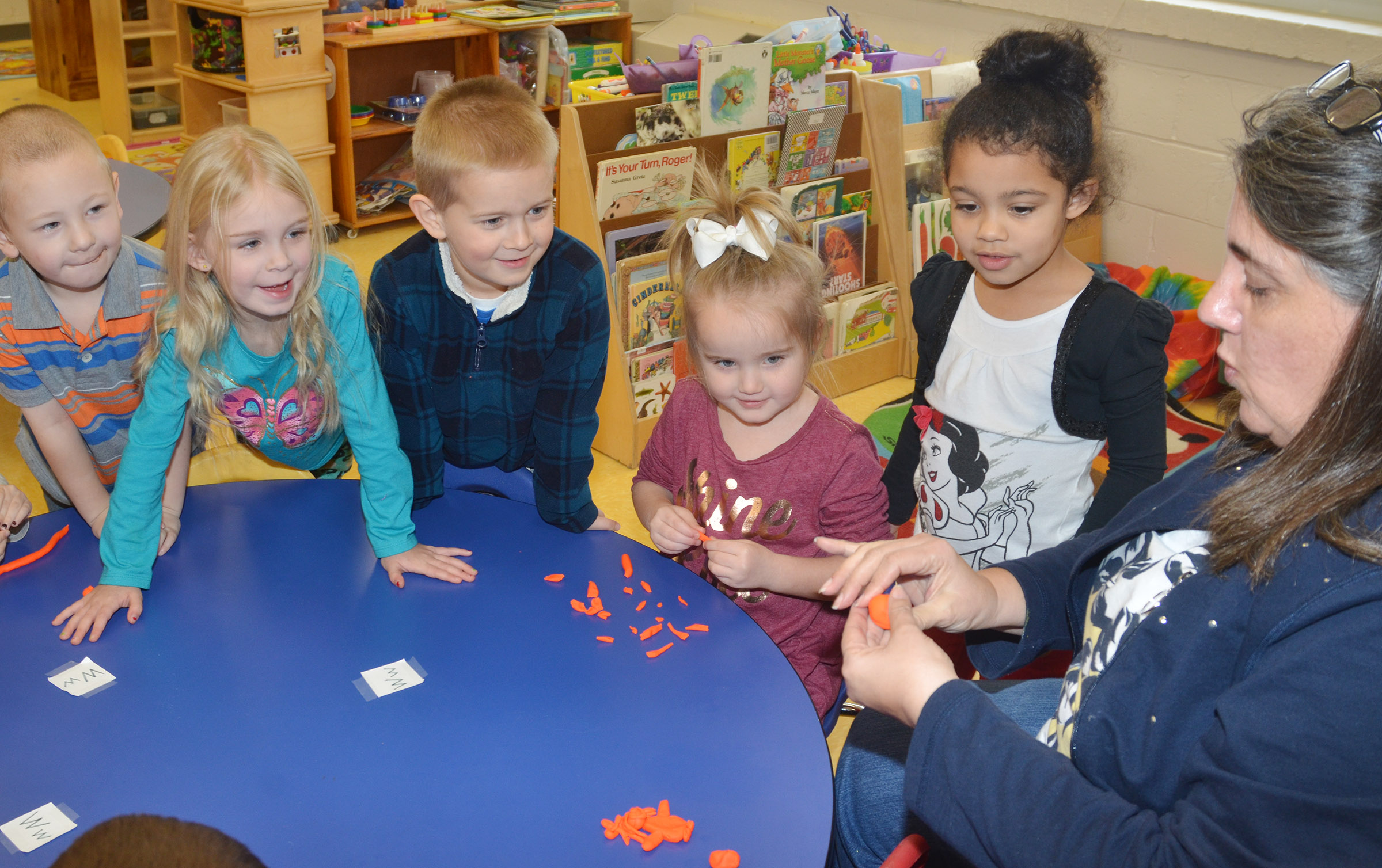 CES preschool teacher Sherry Cowherd makes a wishing well for her students out of Play-Doh. From left are Cameron Dean, Alinna Bray, Jacob Parrish, Trinity Dye and Rylee Karr.