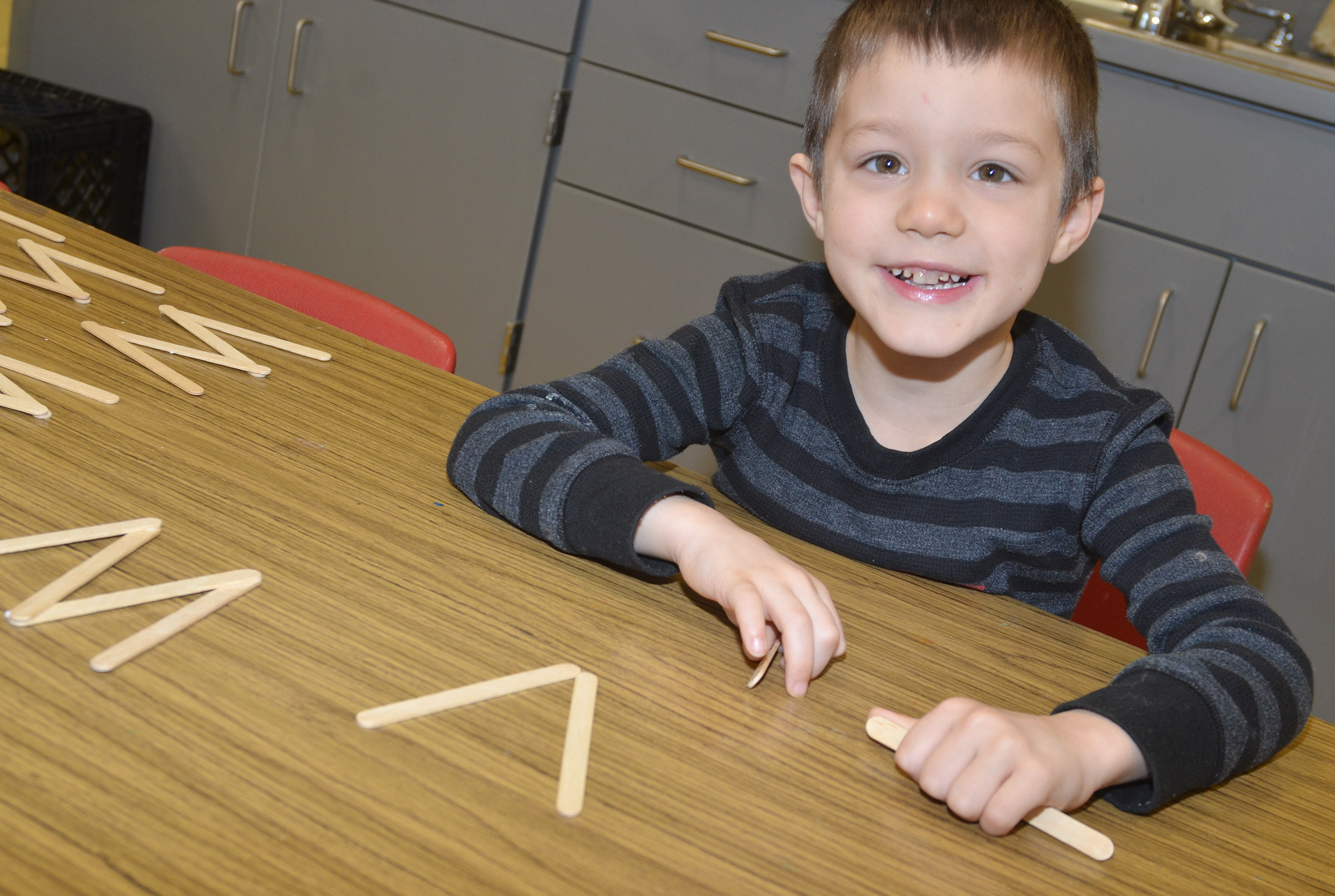 "CES preschool student Levi Ritchie makes half of the letter ""W"" out of Popsicle sticks."