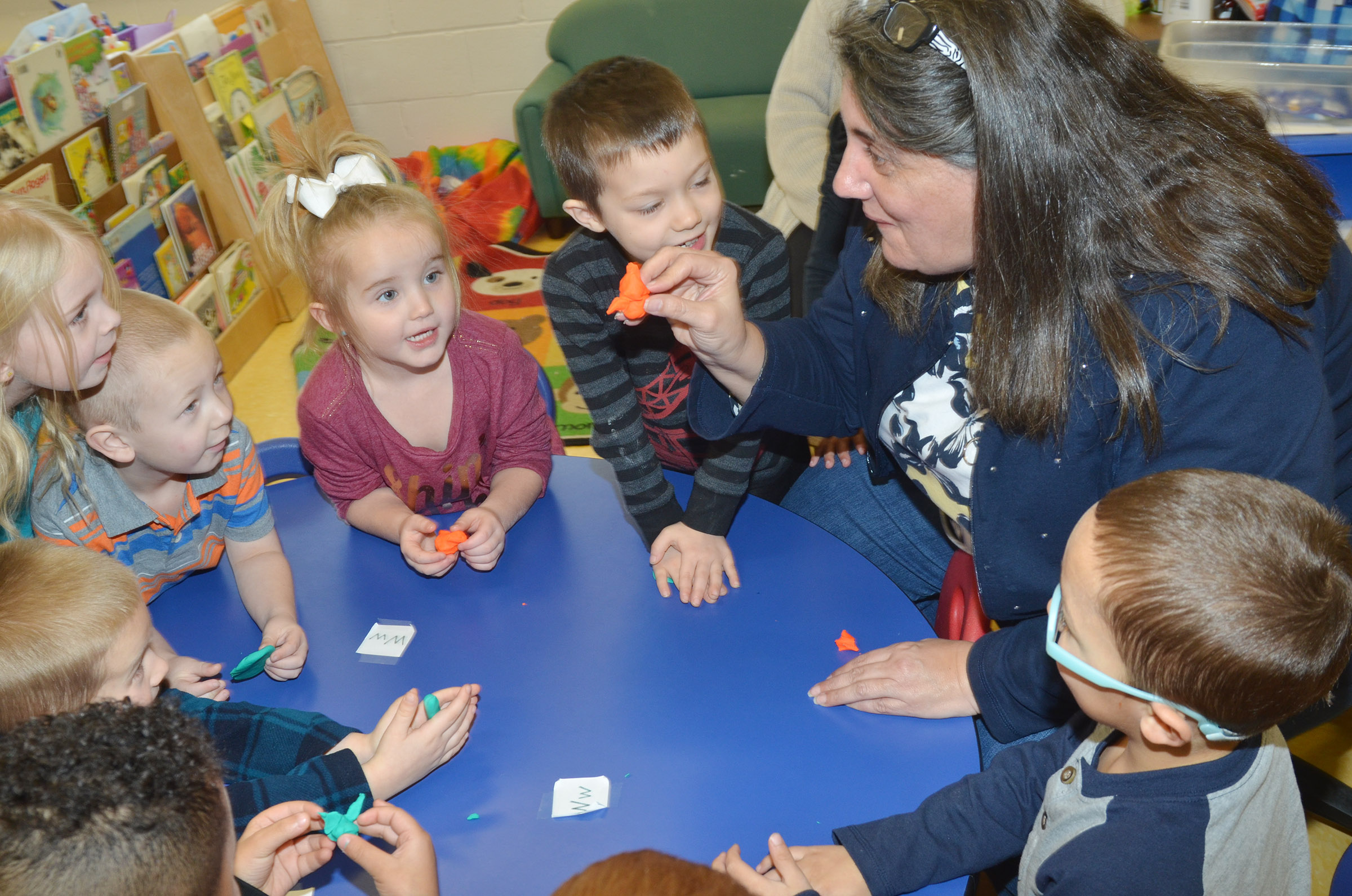 CES preschool teacher Sherry Cowherd makes a witch out of Play-Doh for her students. Clockwise from bottom left are Kingston Cowherd, Jacob Parrish, Alinna Bray, Cameron Dean, Trinity Dye, Levi Ritchie and Chanler Mann.