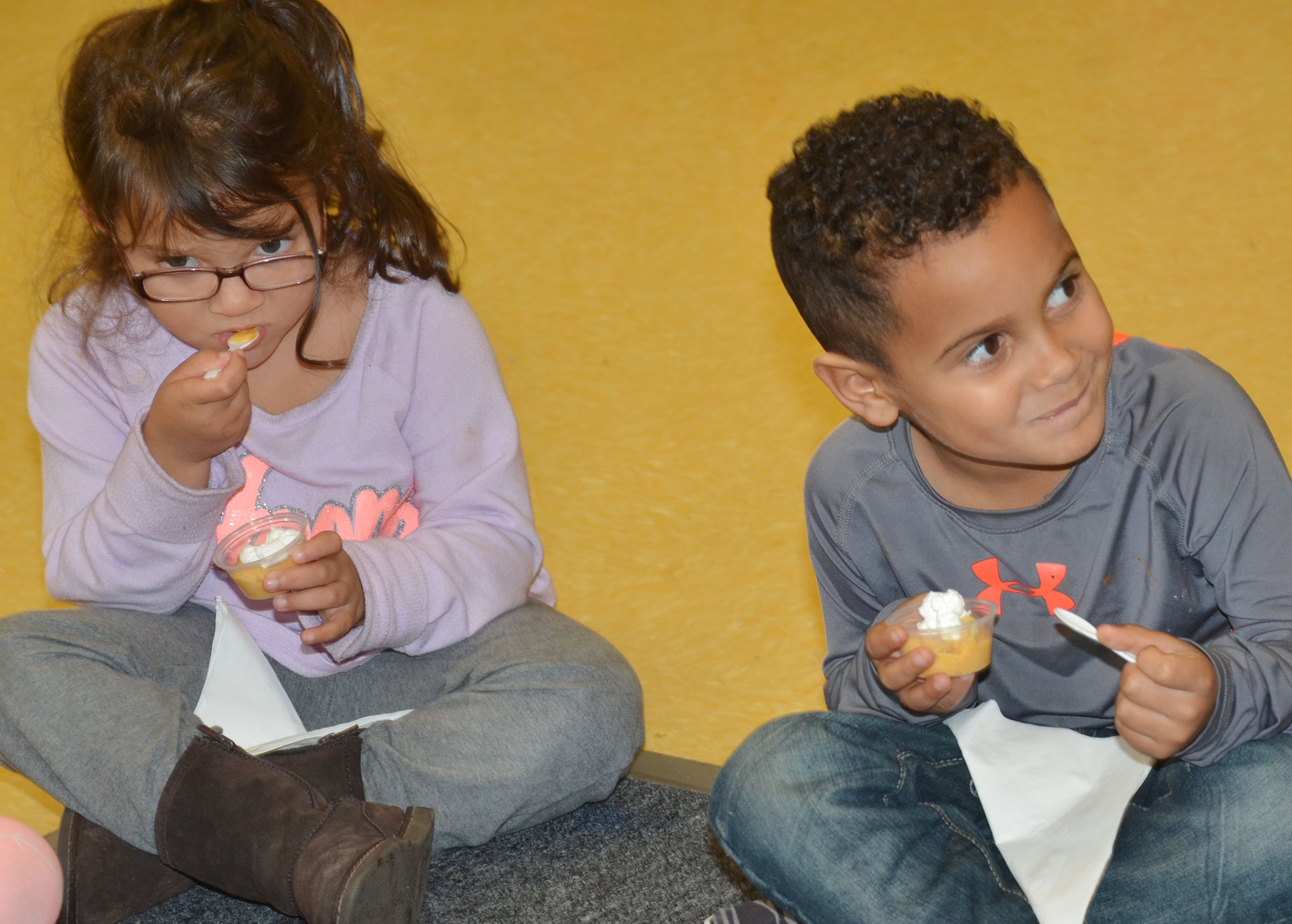 CES preschool student Kingston Cowherd smiles as he samples sweet potato pudding. At left is his classmate, Addisyn Taylor.