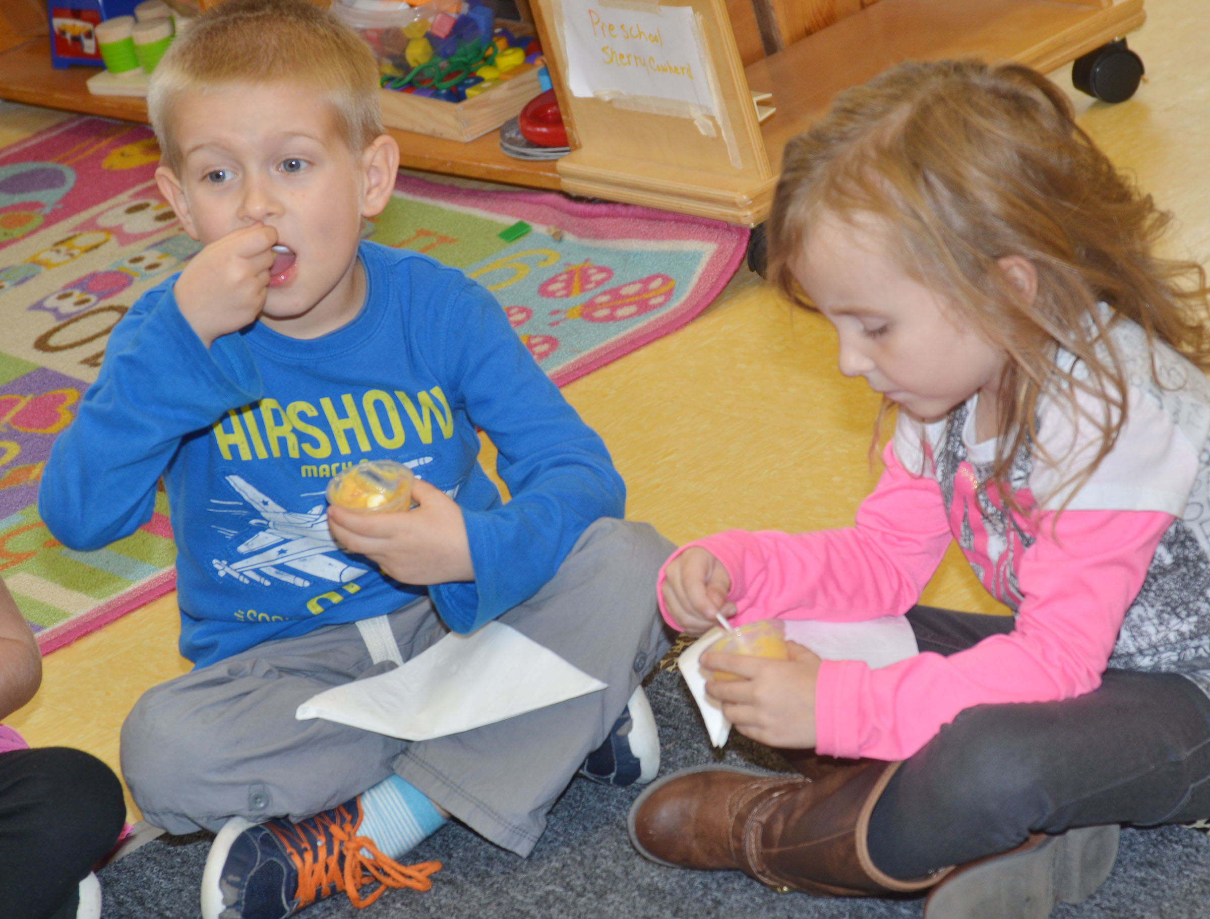 CES preschool students Jacob Parrish, at left, and Tabitha Leggett sample sweet potato pudding.