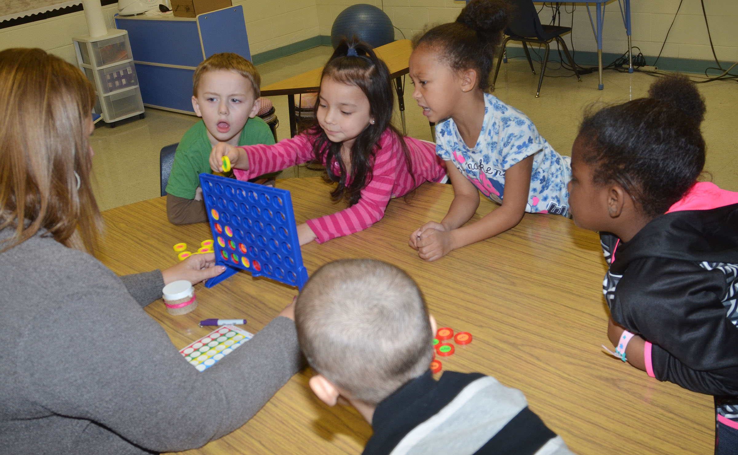 Jane Parrott, an exceptional child educator at CES, plays Connect Four with kindergarten students to help them learn letters and words.