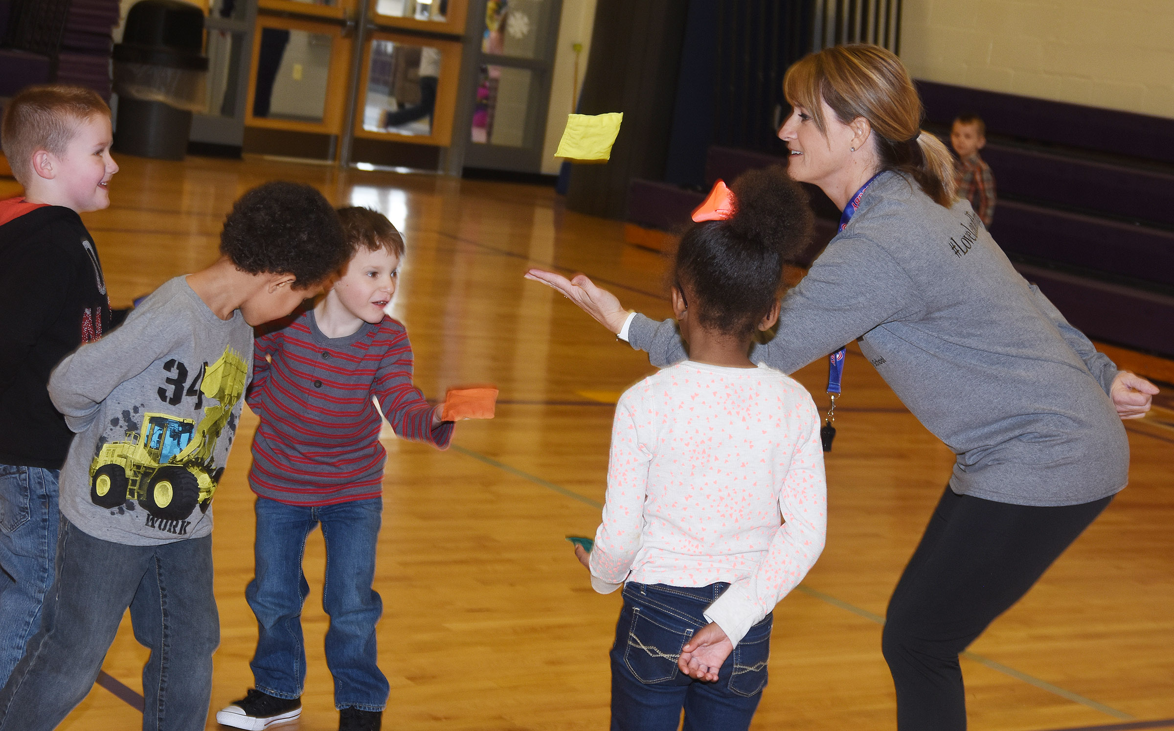 CES physical education teacher Vanessa Adkins shows kindergarteners how to throw and catch a bean bag.