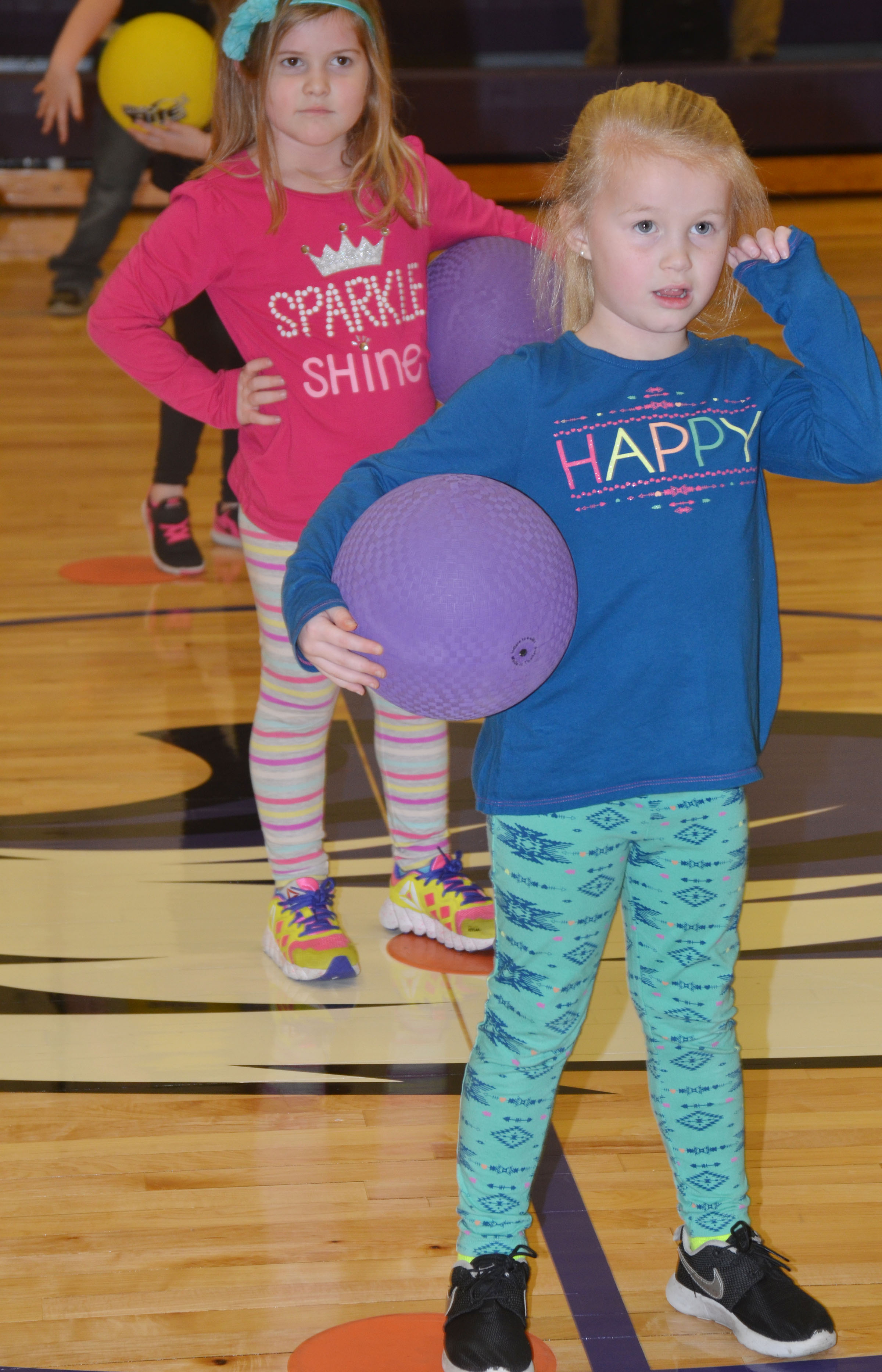 CES kindergarteners Aubreigh Knifley, at left, and Lillie Judd listen as they prepare to practice dribbling in the new CES gymnasium.
