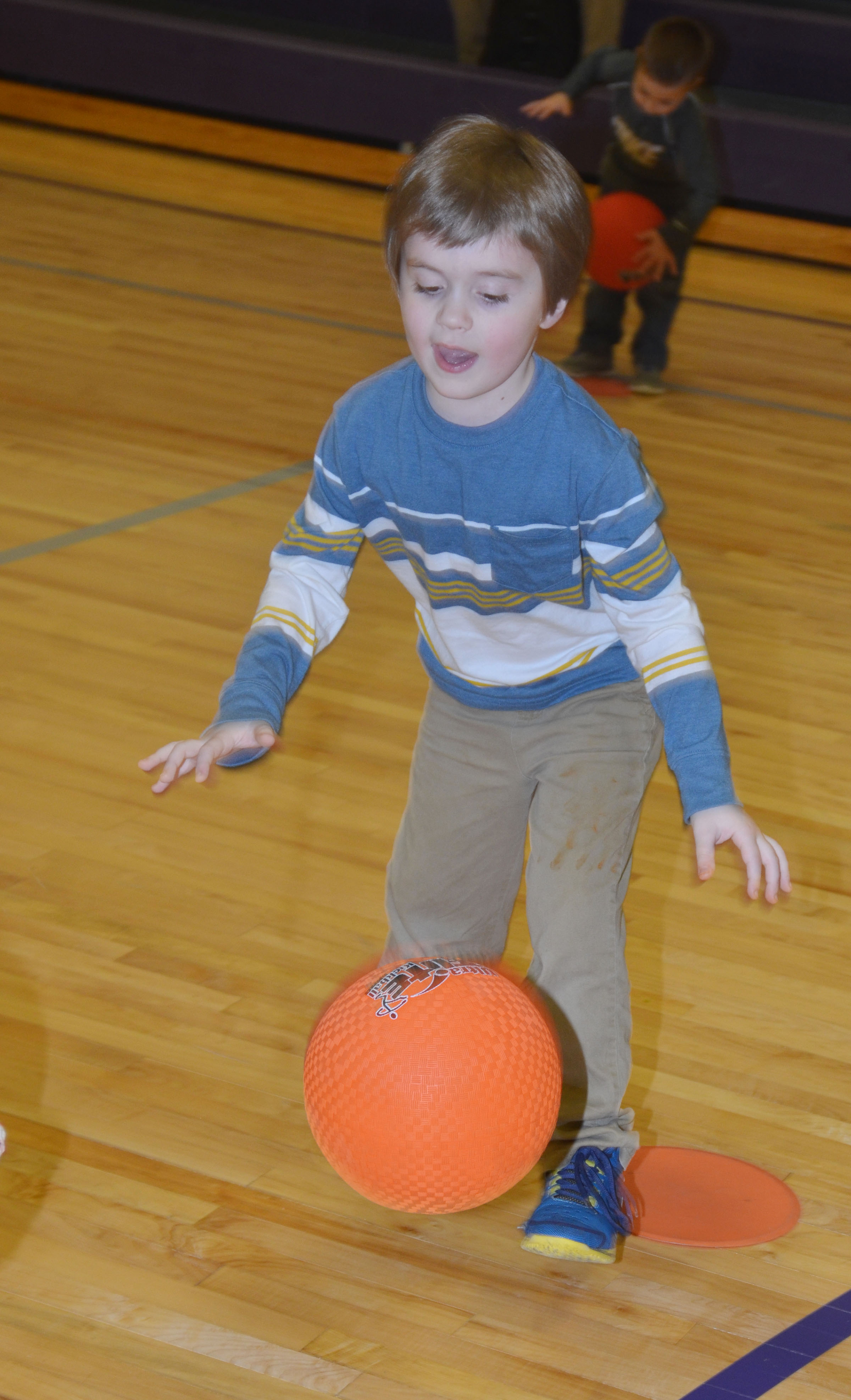 CES kindergartener Gavin Williams practices dribbling in the new CES gymnasium.