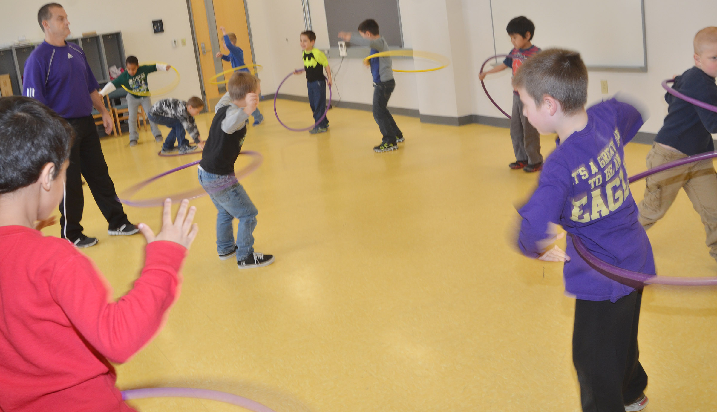 CES PE teacher Lynn Kearney watches as his students practice their hula hoop skills.