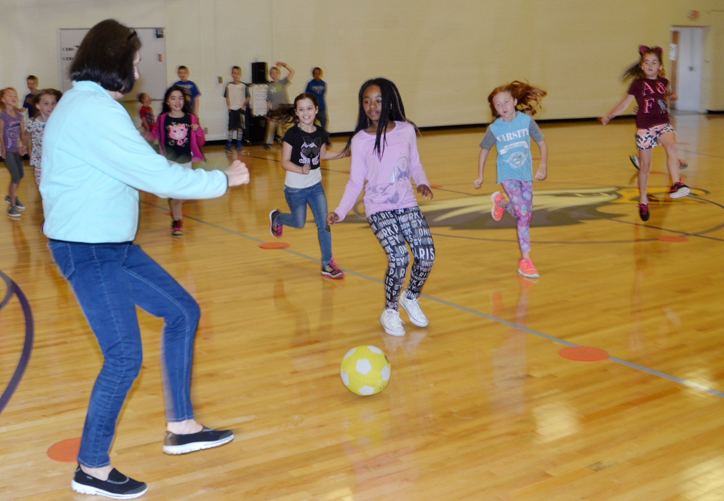 CES instructional assistant Ann Callison plays soccer with third-graders.