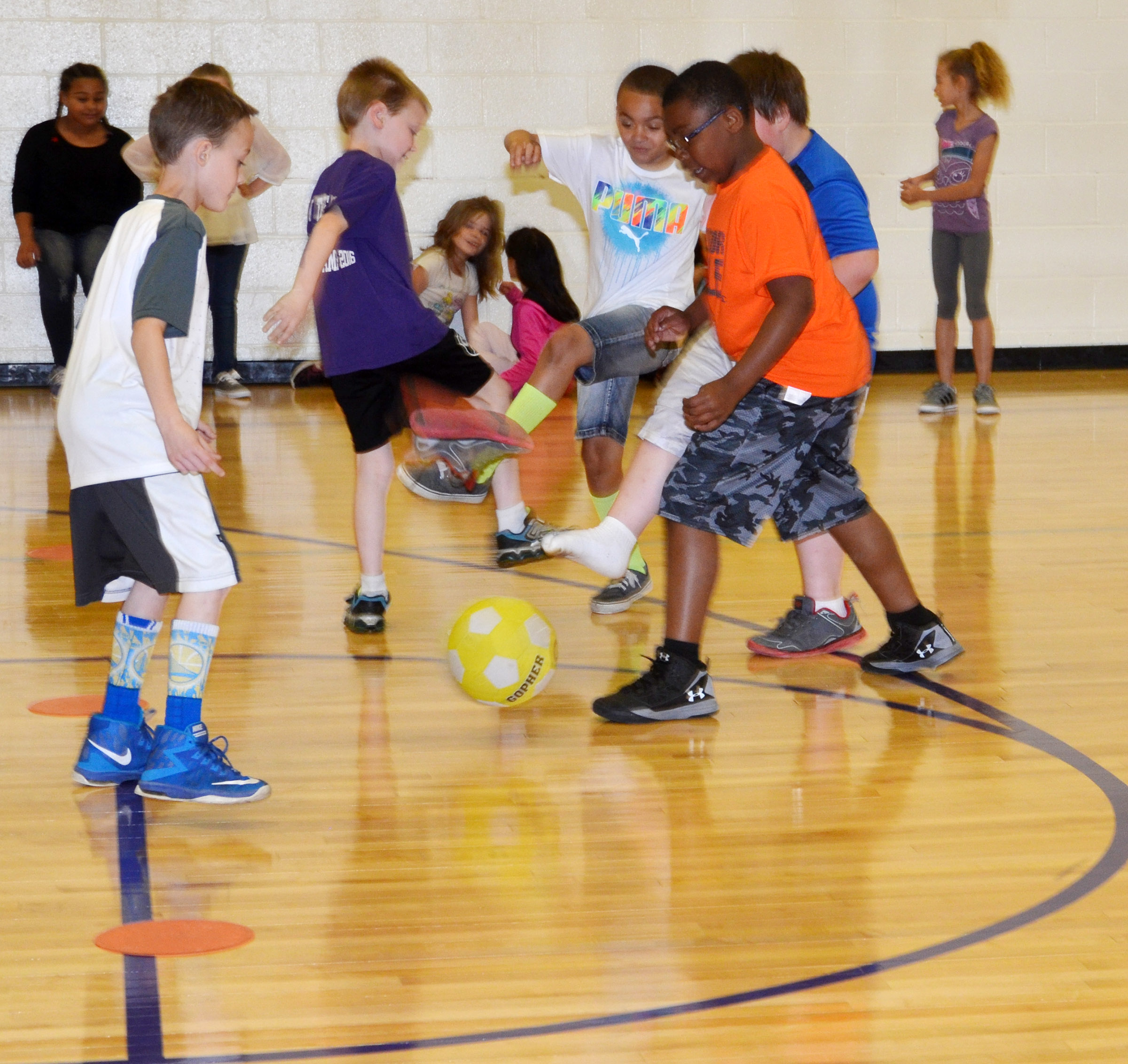 CES third-graders kick the soccer ball.