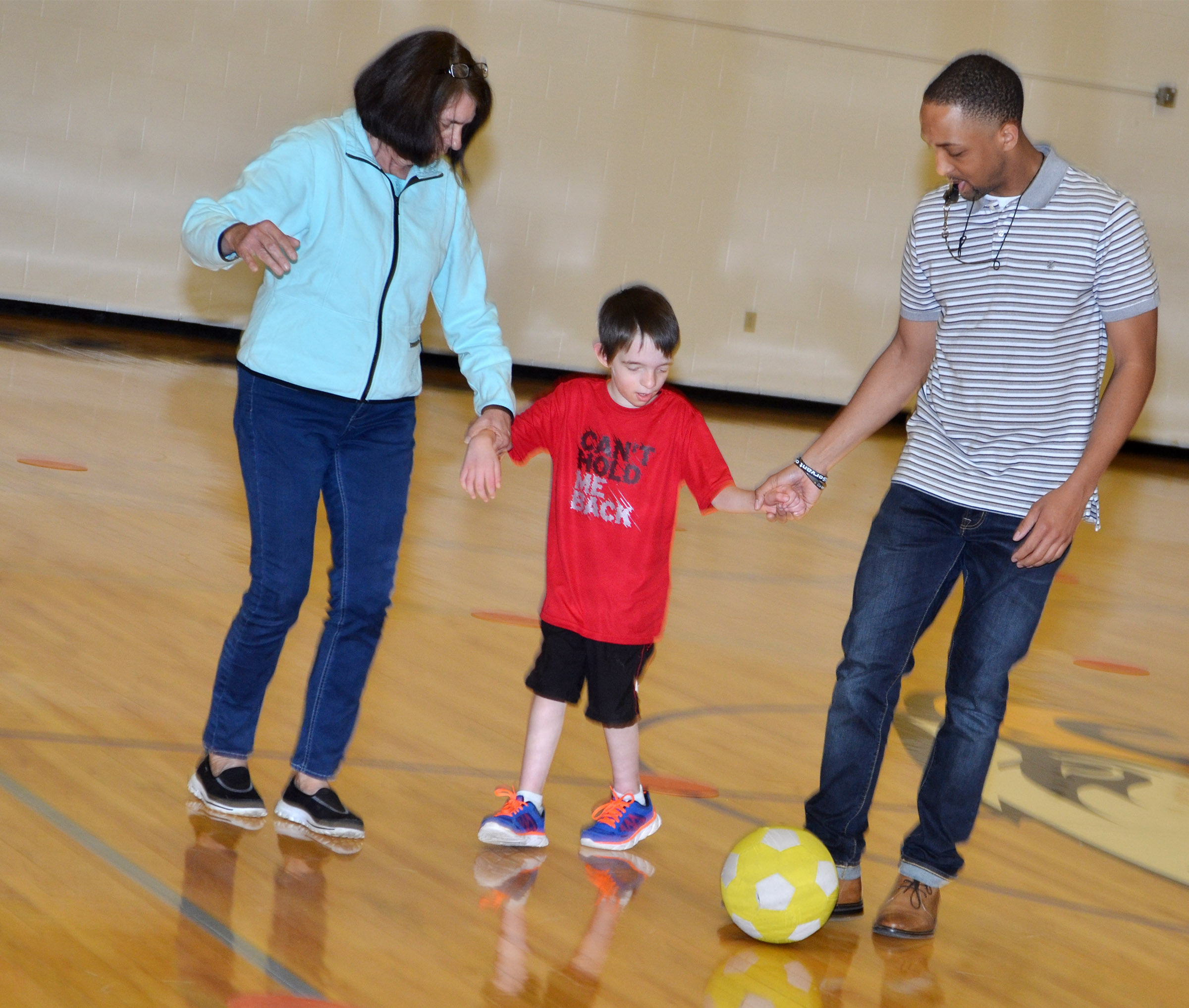 CES instructional assistant Ann Callison, at left, and Campbellsville University student teacher George Boyd help fourth-grader Noah Nelson kick the soccer ball.