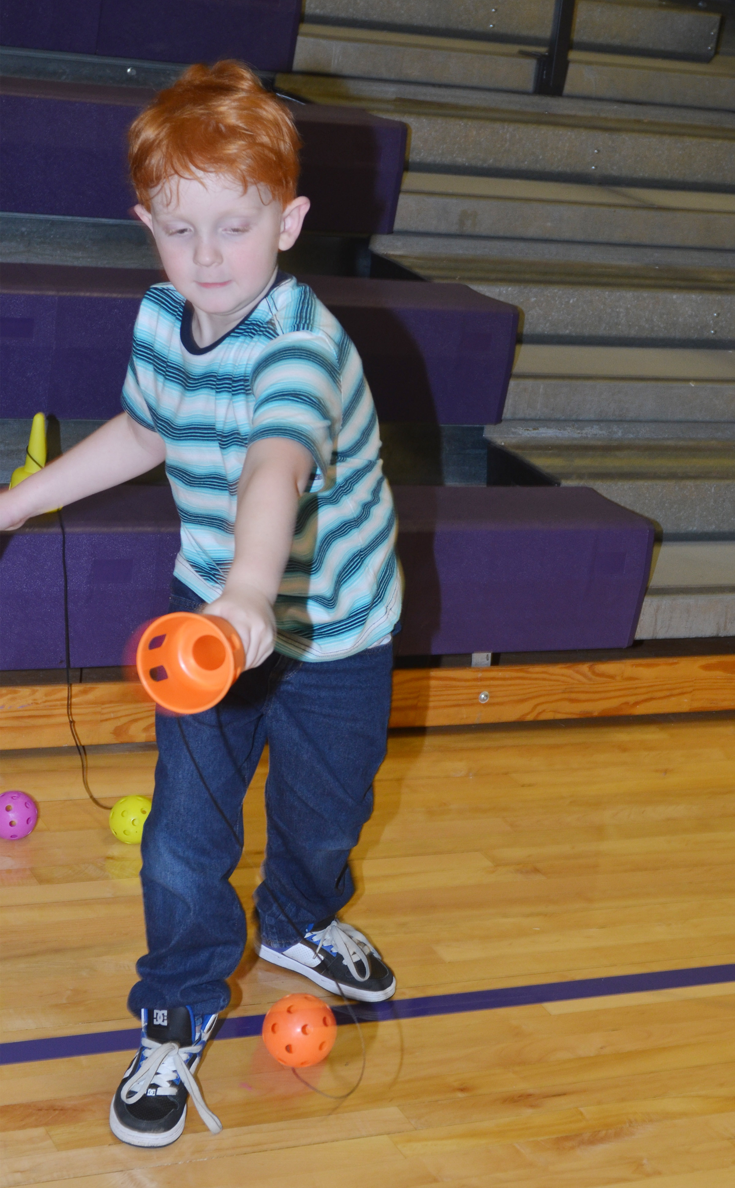 CES second-grader Gavin Martin tries to catch a ball in a cup.