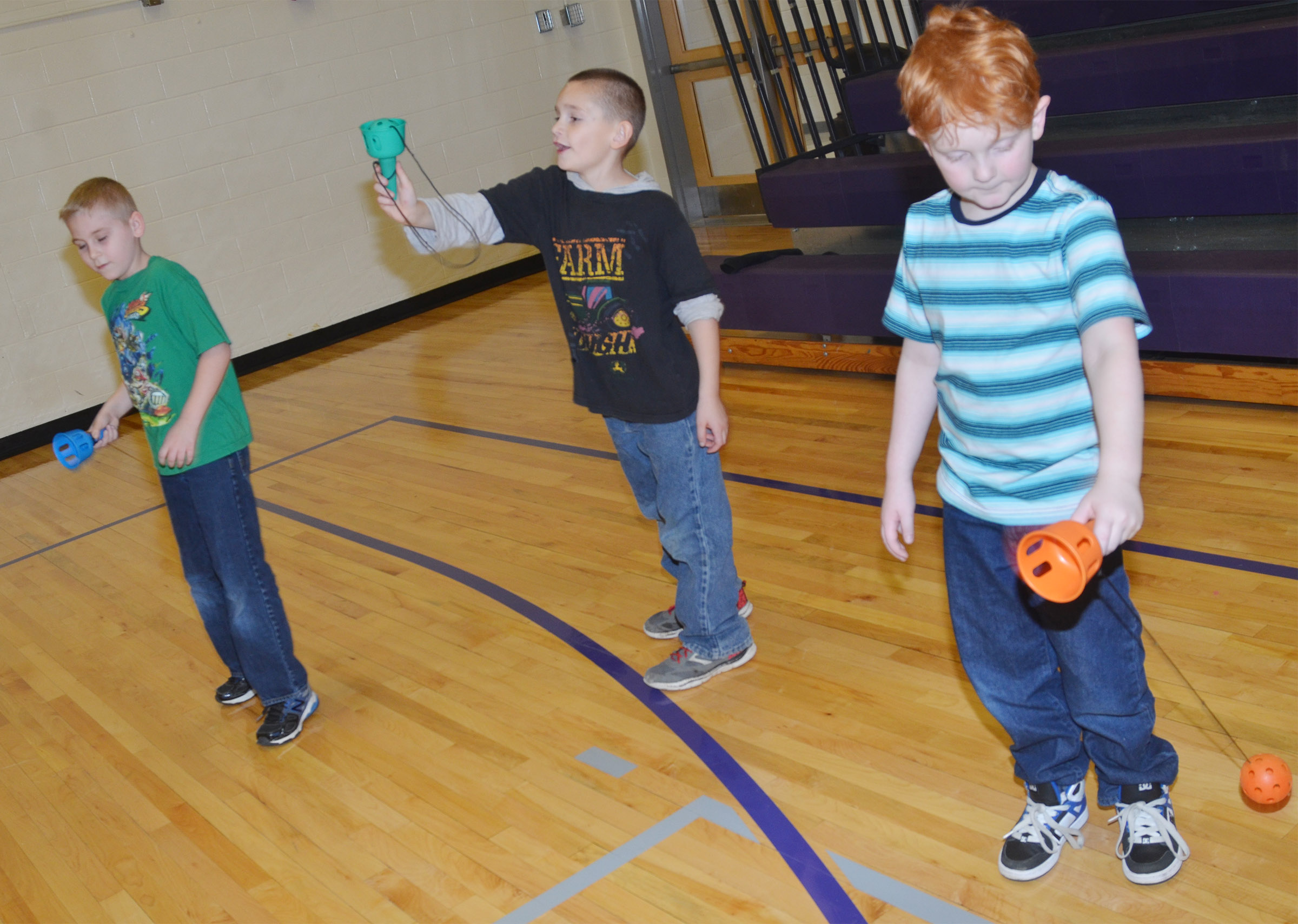 From left, CES second-graders Joseph Greer, Sean Welch and Gavin Martin try to catch a ball in their cups.