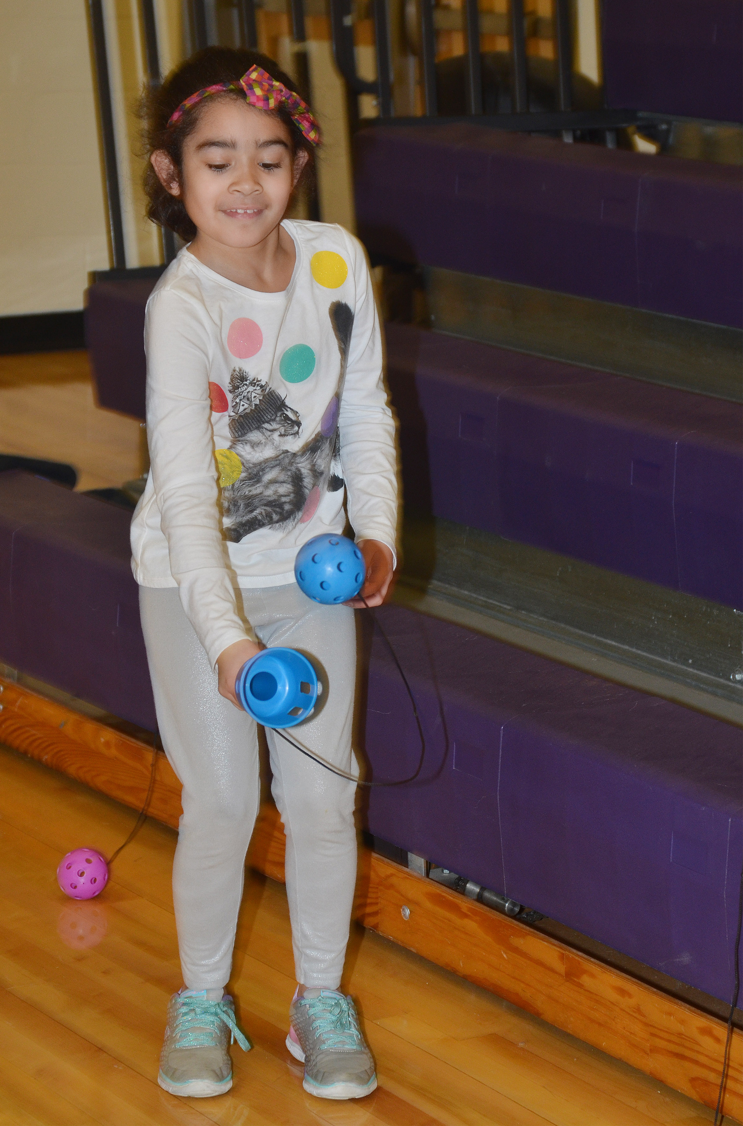 CES second-grader Sophia Santos tries to catch a ball in a cup.