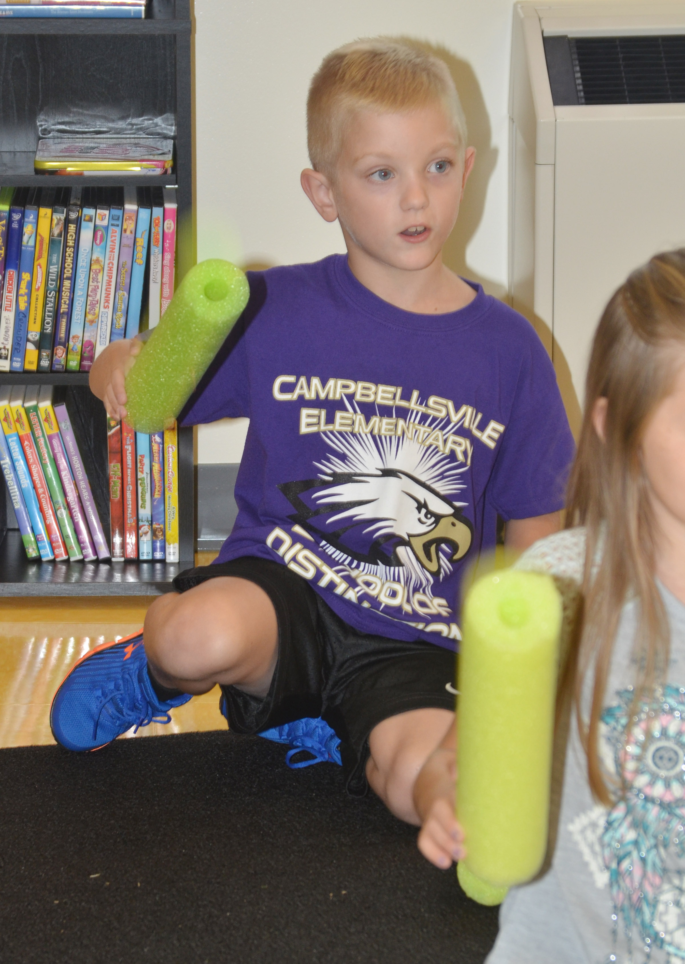 CES second-grader Evan Cundiff plays a rhythm with pool noodles.