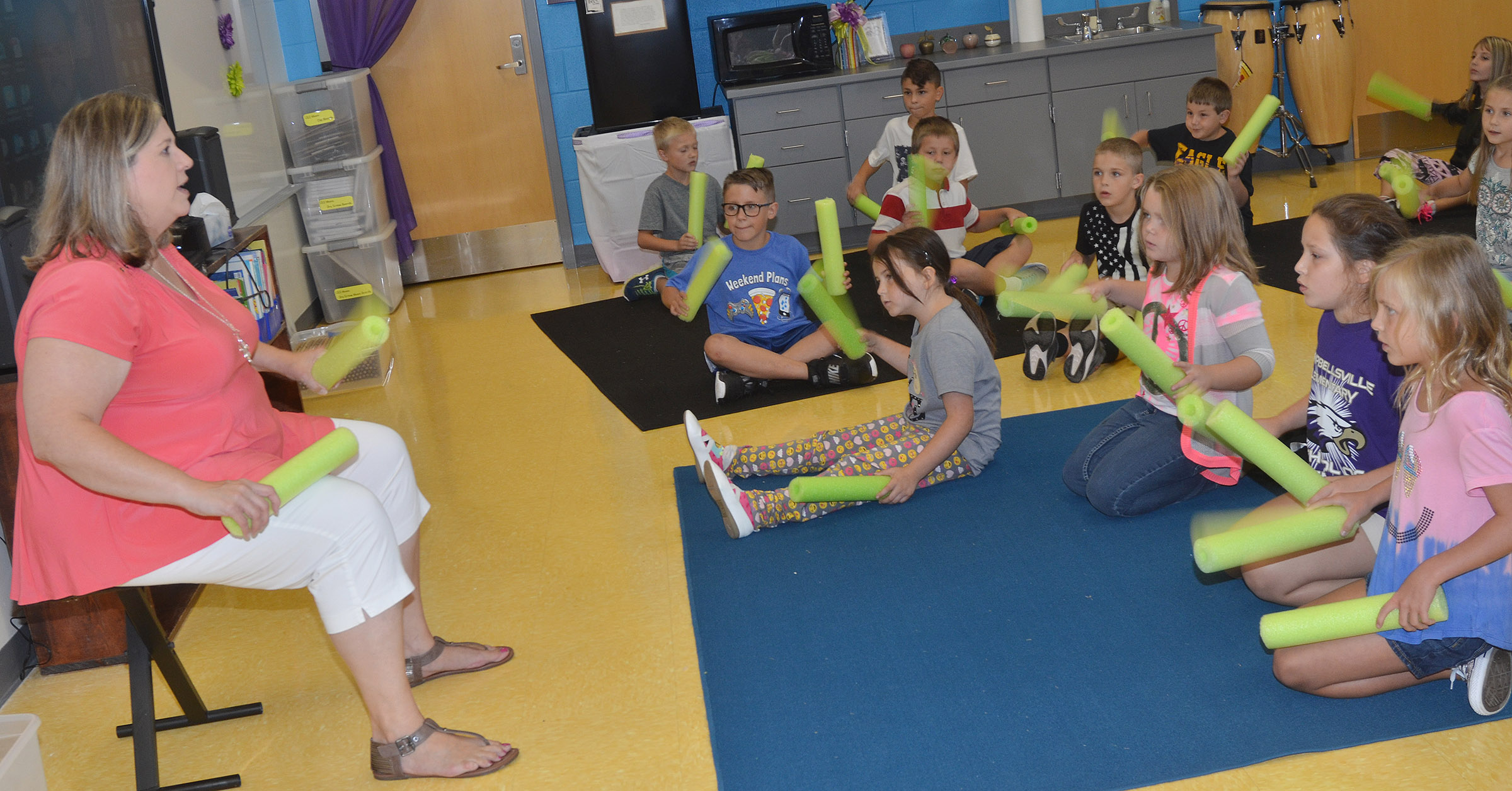 CES music teacher Cyndi Chadwick leads her students as they play a rhythm with pool noodles.
