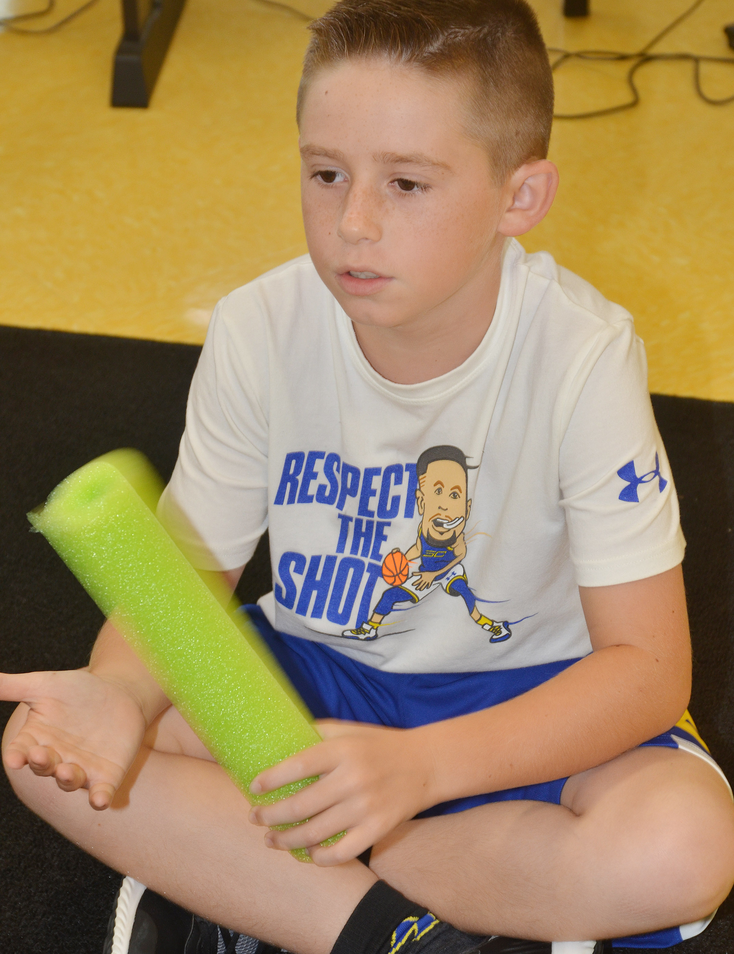 CES second-grader Lanigan Price plays a rhythm with pool noodles.