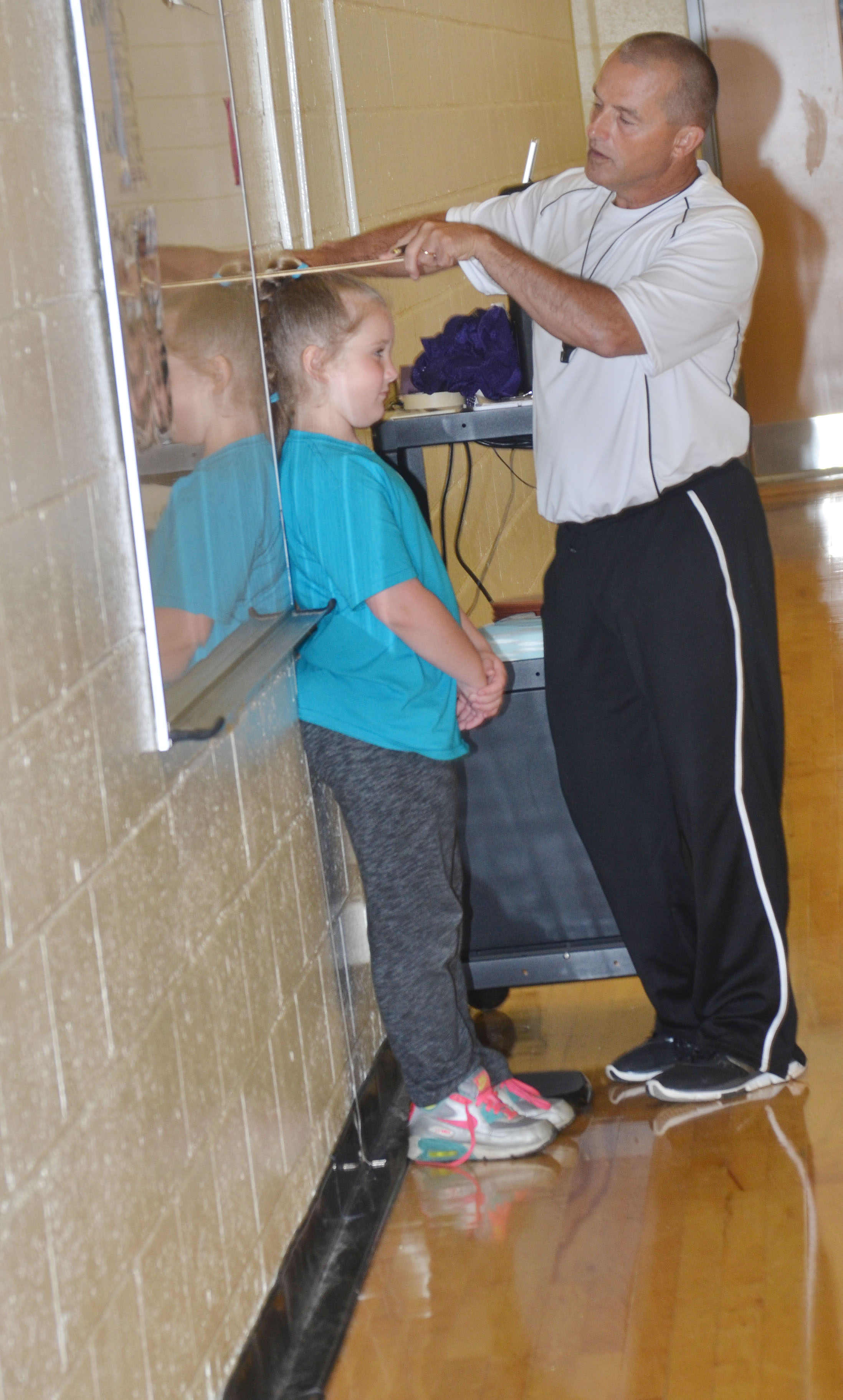 CES physical education teacher Lynn Kearney measures third-grader Kiera Bailey.
