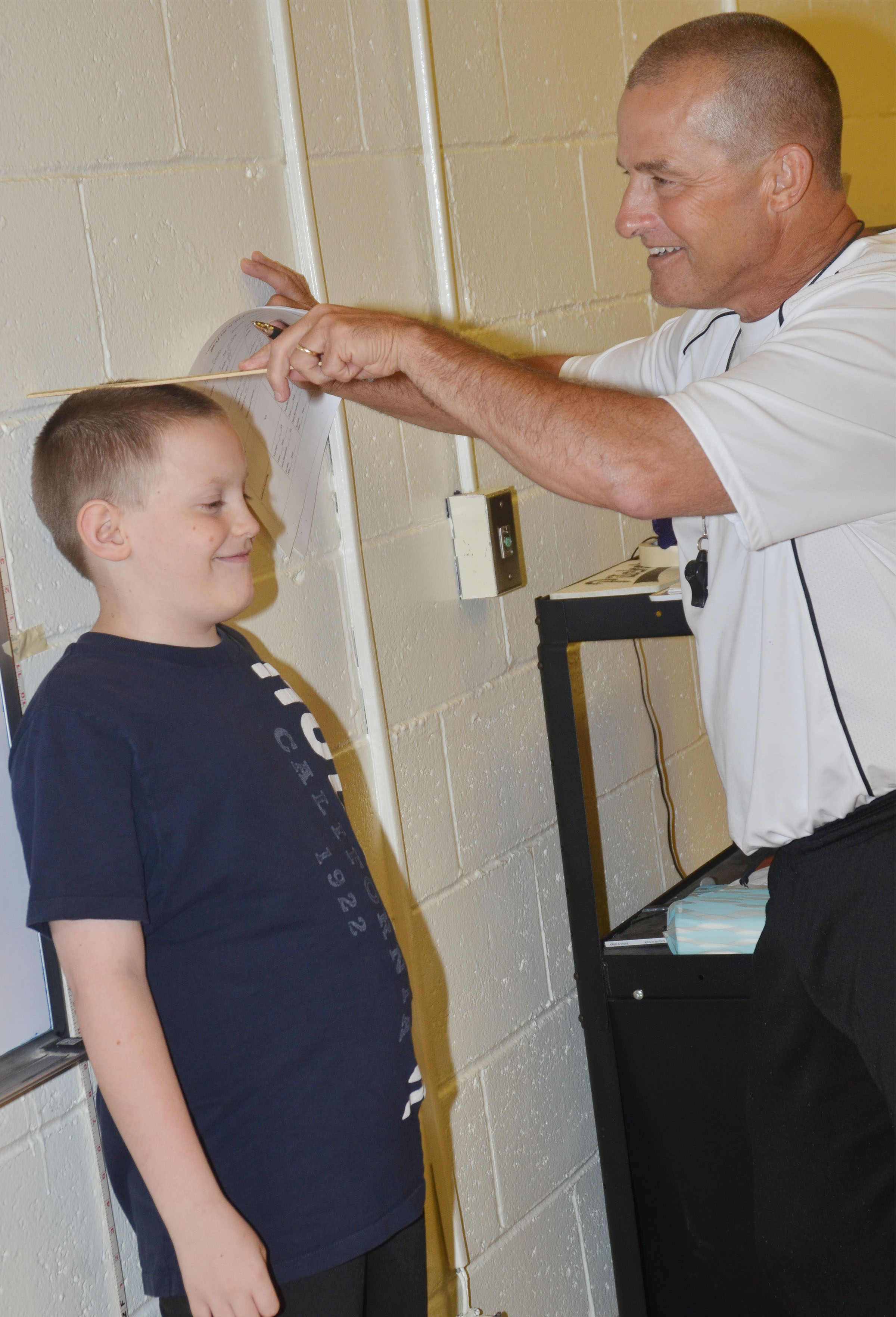CES physical education teacher Lynn Kearney records third-grader Bobby Engle's height.
