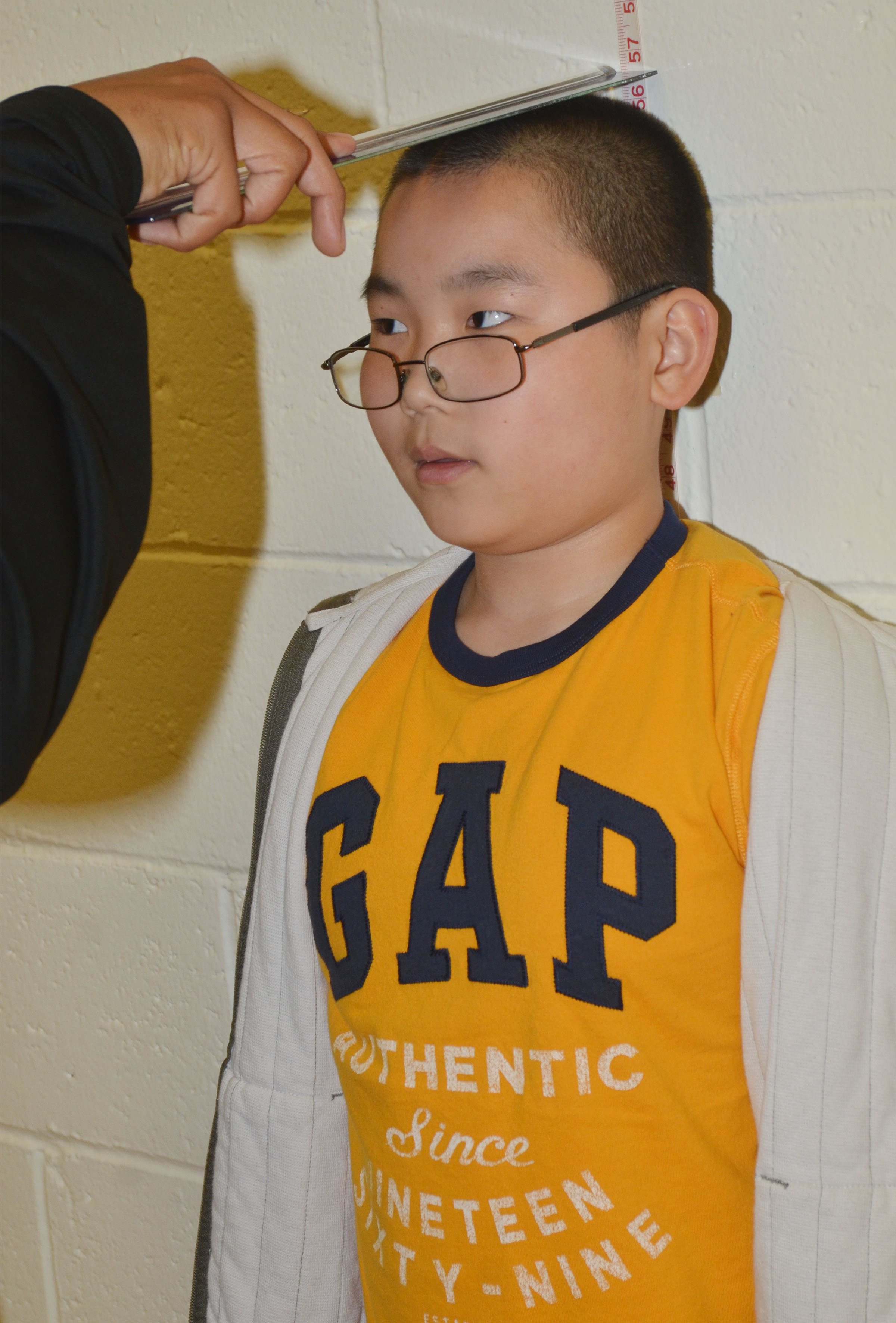 CES third-grader Martin Yang stands still as student teacher George Boyd records his height.