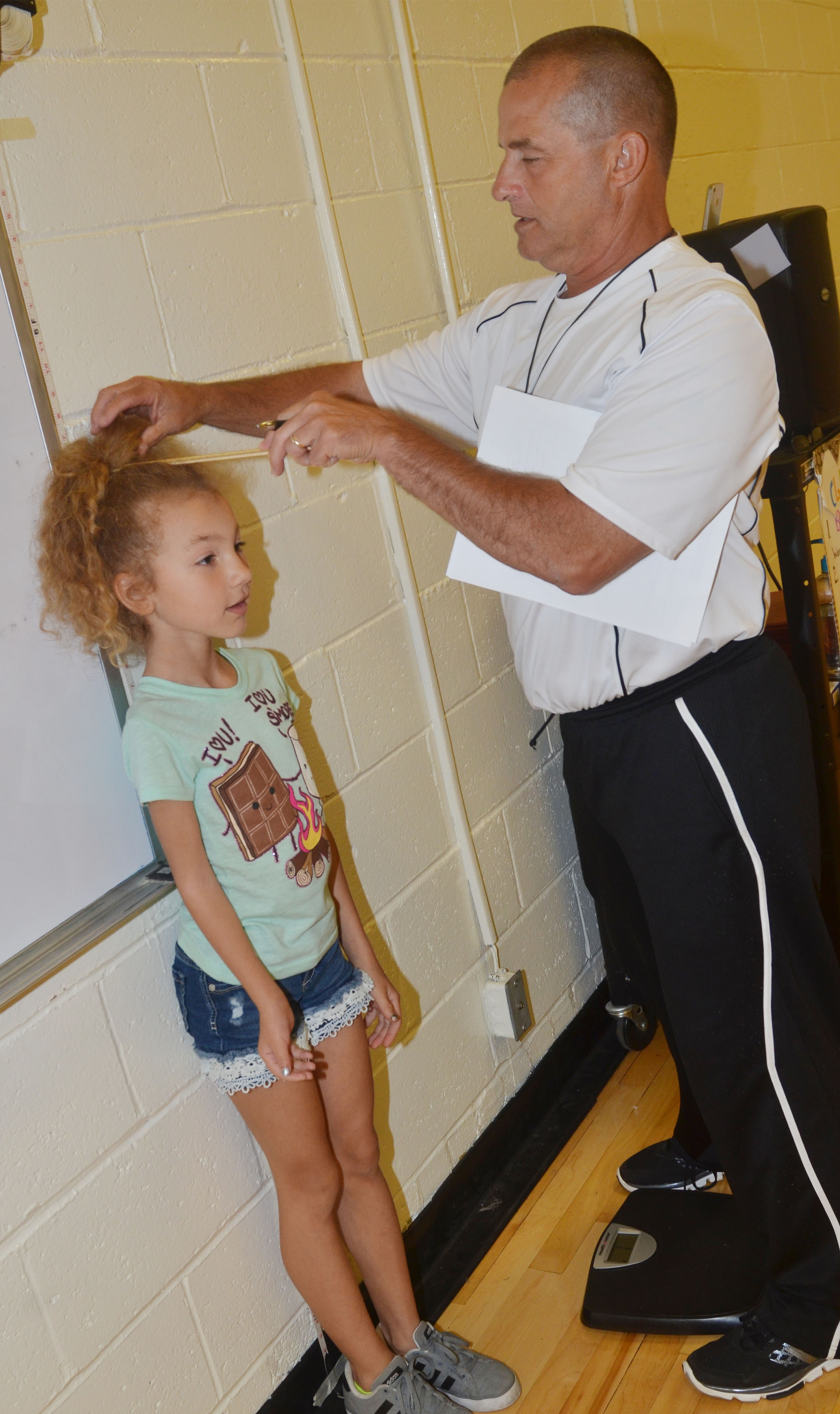 CES physical education teacher Lynn Kearney records third-grader Raelyn Dunn's height.