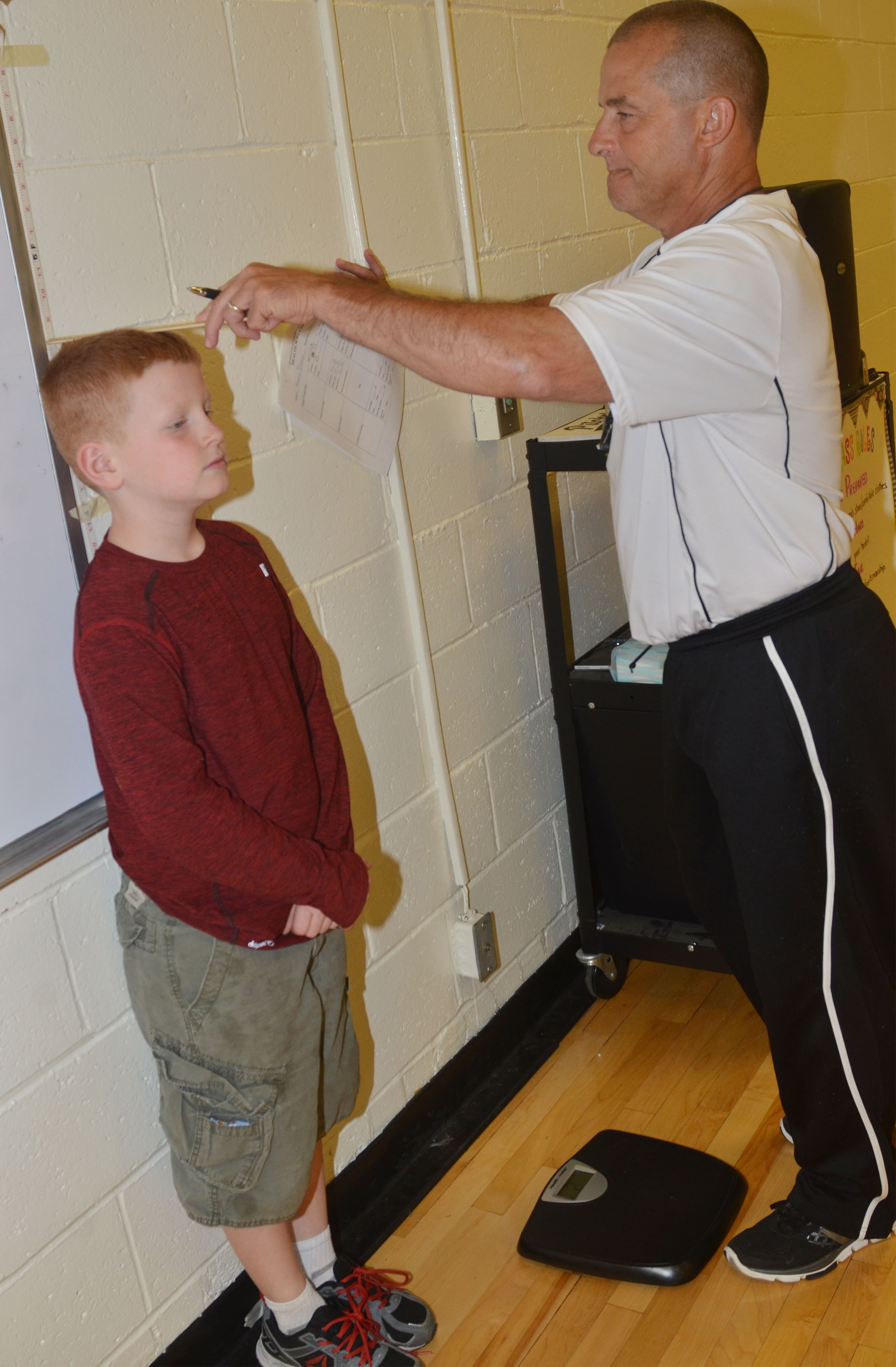 CES physical education teacher Lynn Kearney records Westin Dudgeon's height.