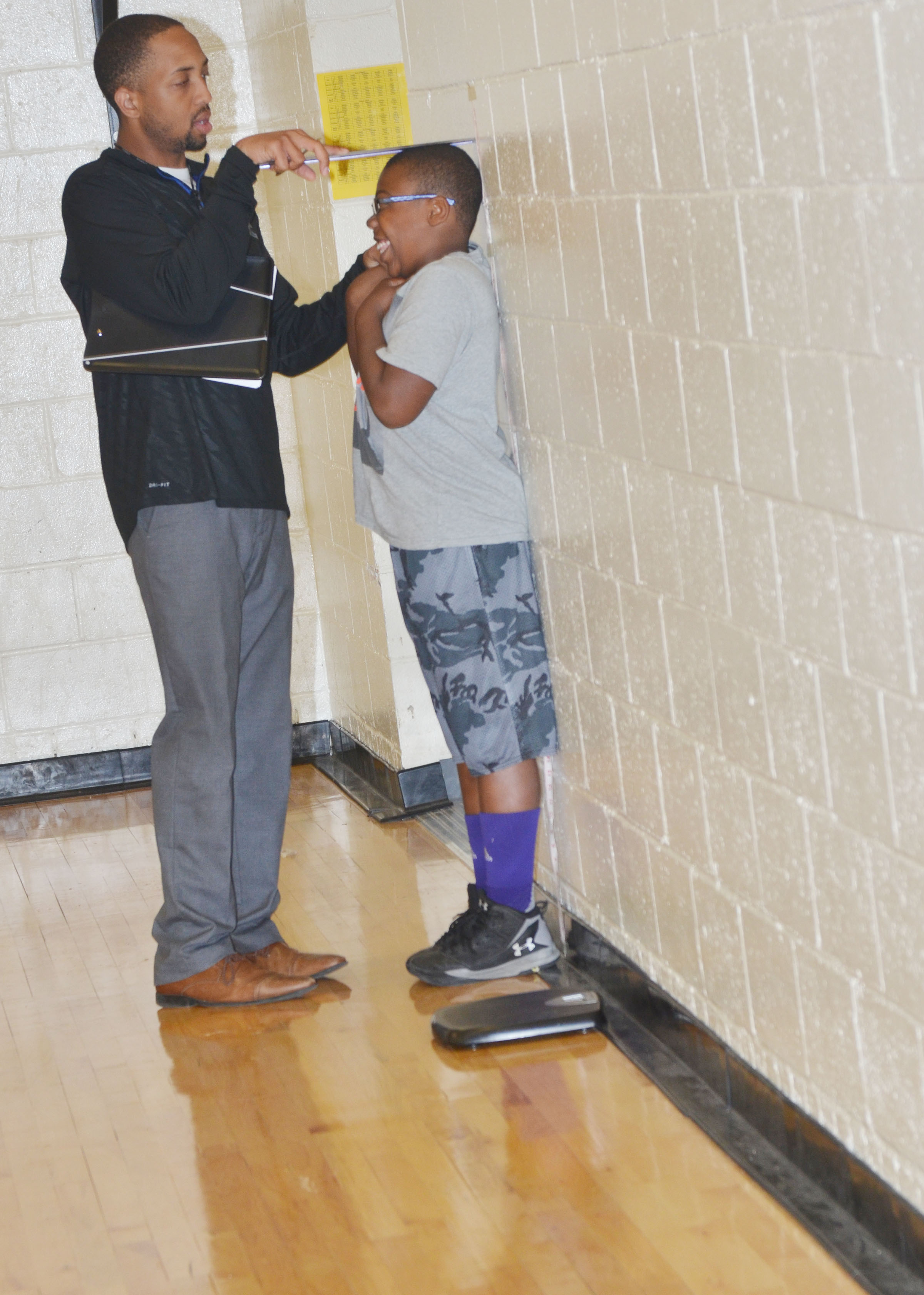 CES student teacher George Boyd records third-grader Austin Sloan's height.