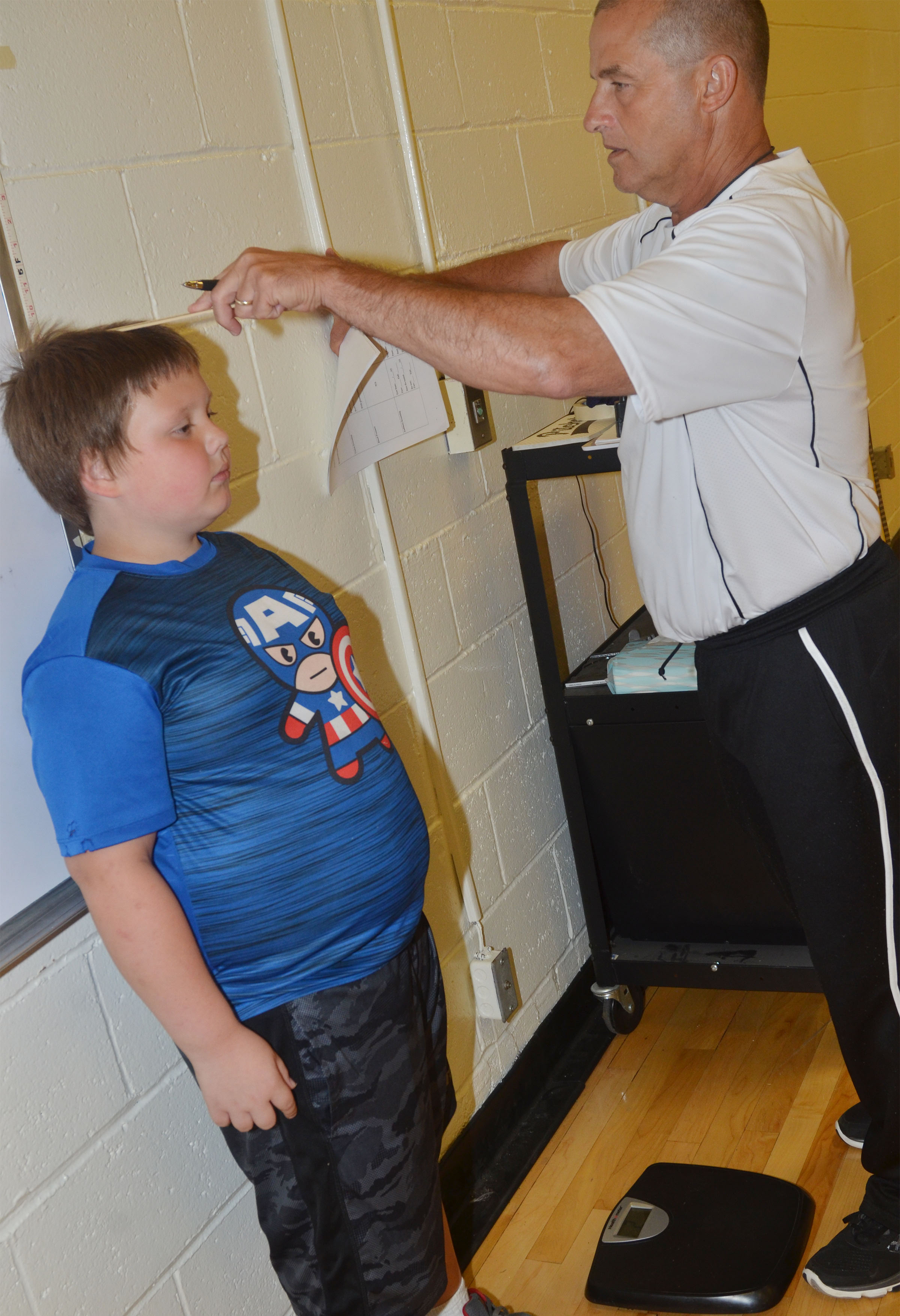 CES physical education teacher Lynn Kearney measures third-grader Jace Cox.