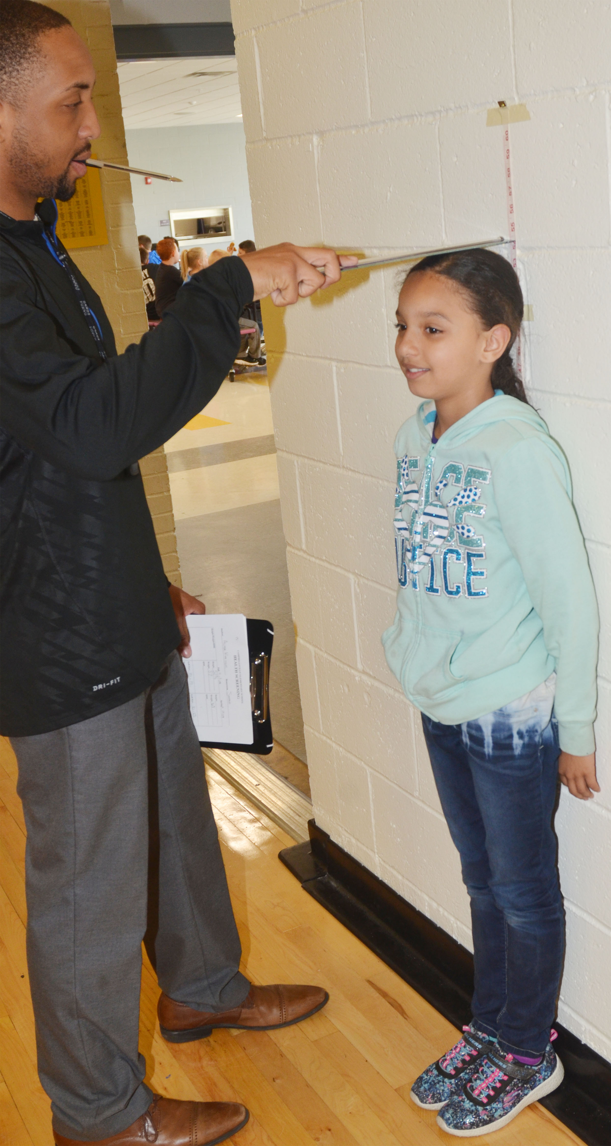 CES student teacher George Boyd records third-grader Alyssa Knezevic's height.