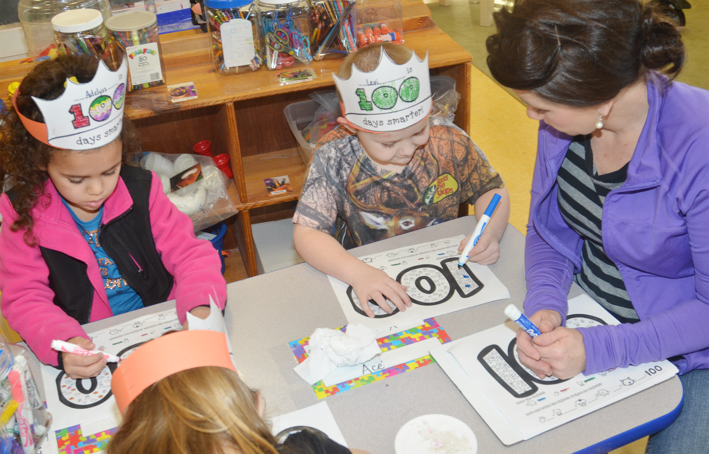 CES preschool assistant Beth Sandidge helps Adelyn Litsey, at left, and Levi Dye count to 100 on the 100th day of school.