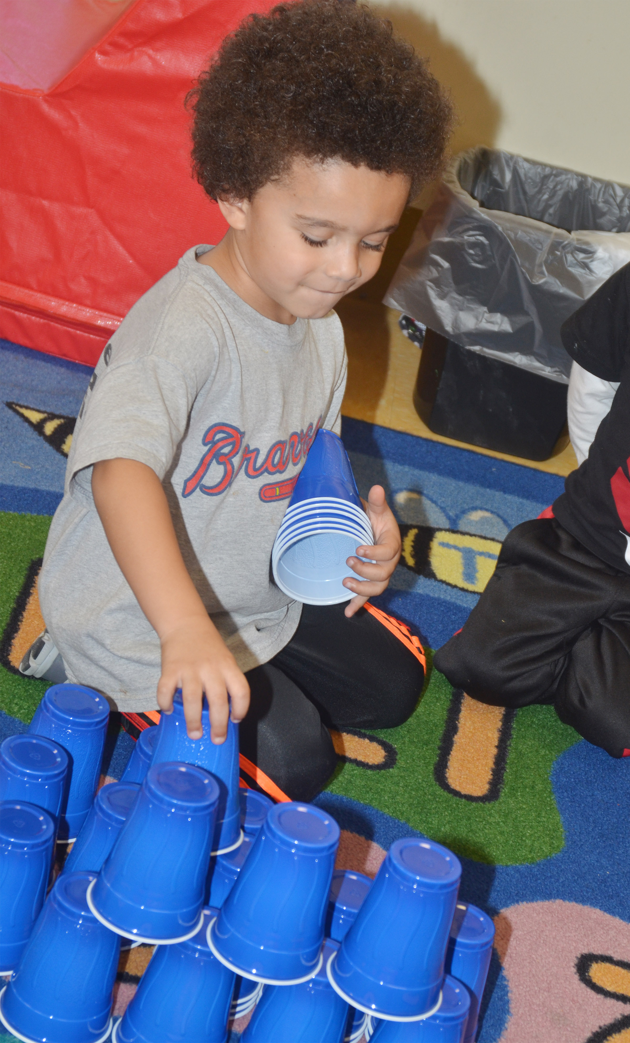 CES preschool student Tyrek Moore stacks cups on the 100th day of school. His class stacked a total of 100 cups.