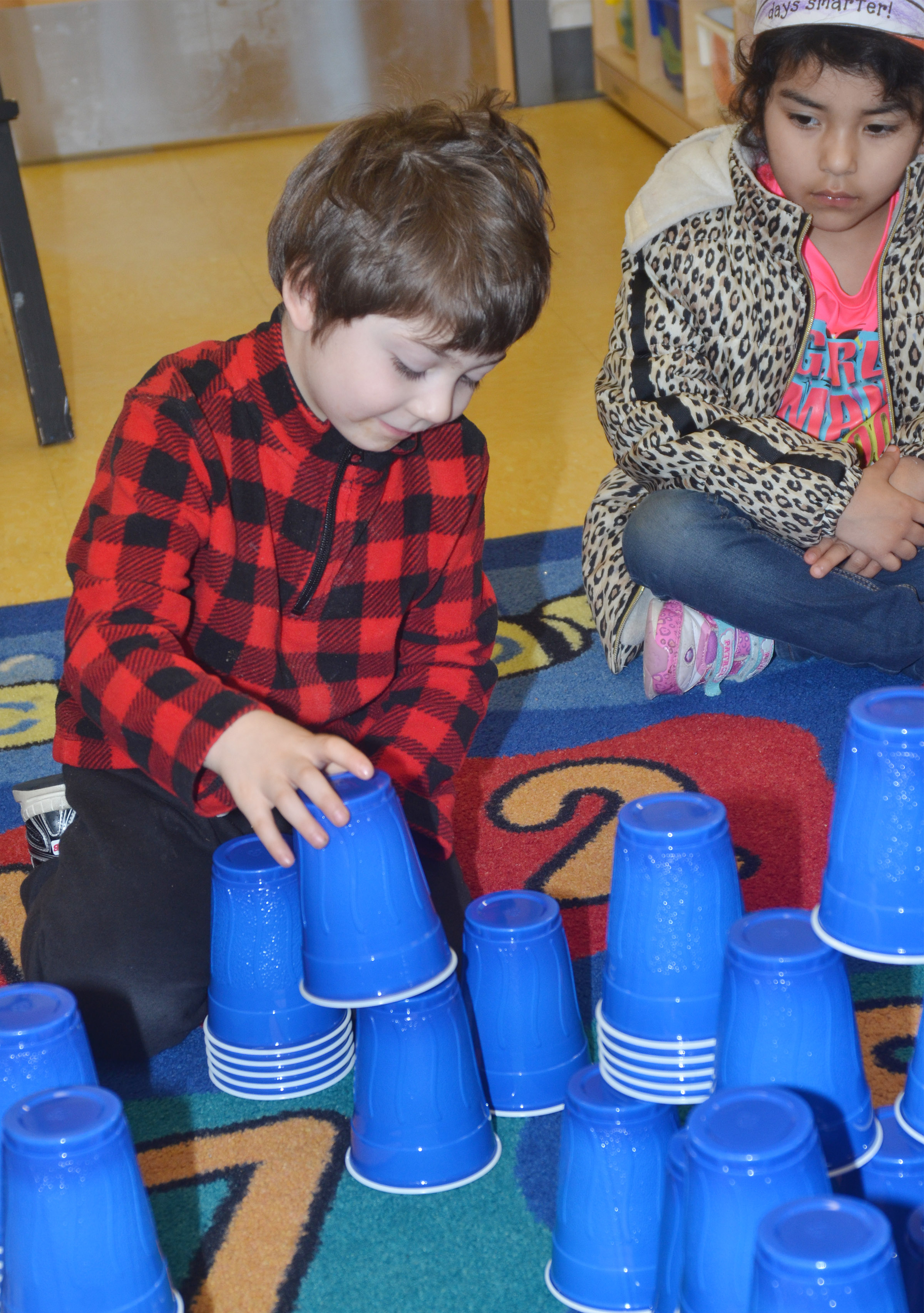 CES preschool student Josiah Dean stacks cups on the 100th day of school. His class stacked a total of 100 cups.