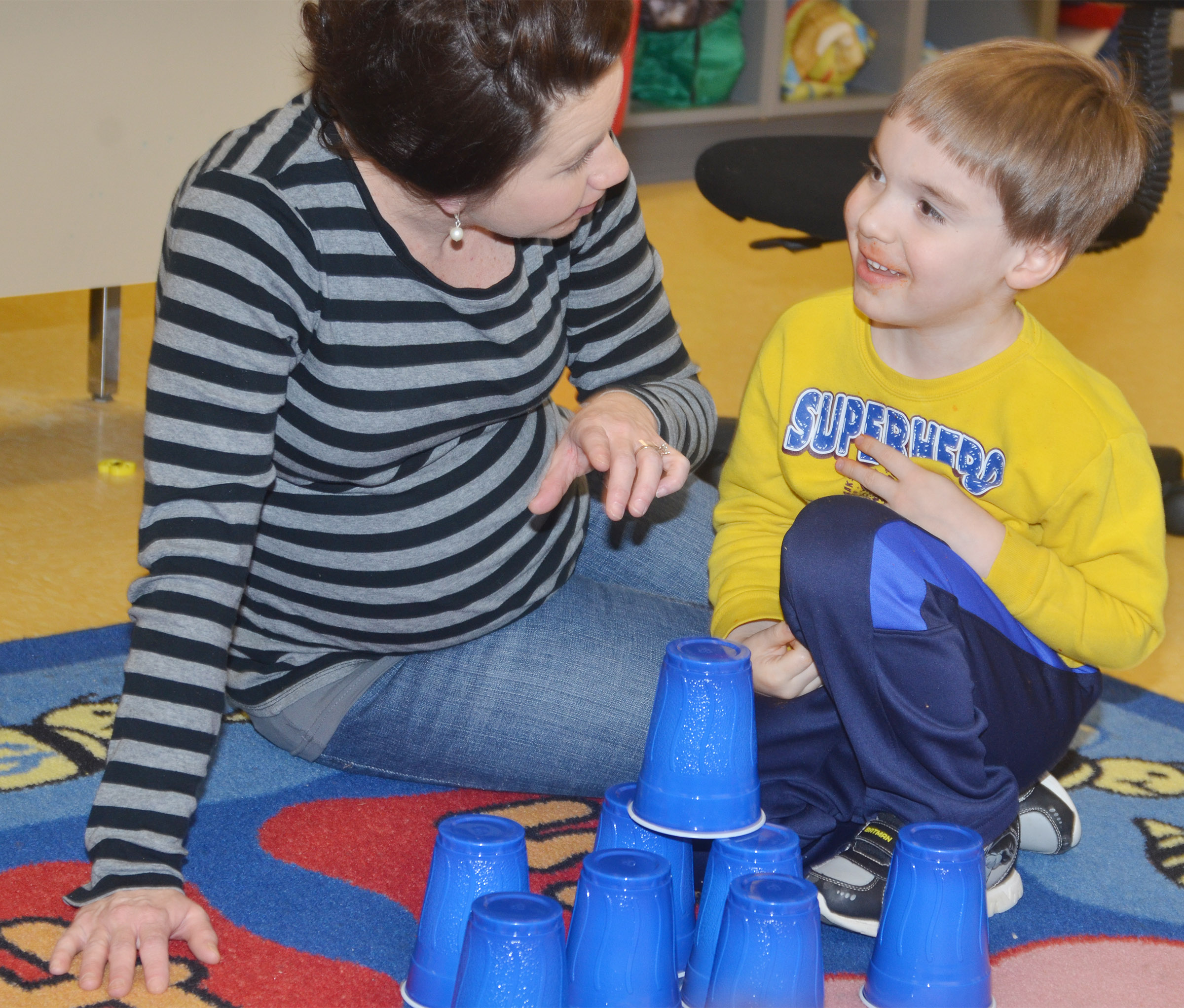 CES preschool assistant Beth Sandidge helps Finley Williams stack cups on the 100th day of school. His class stacked a total of 100 cups.