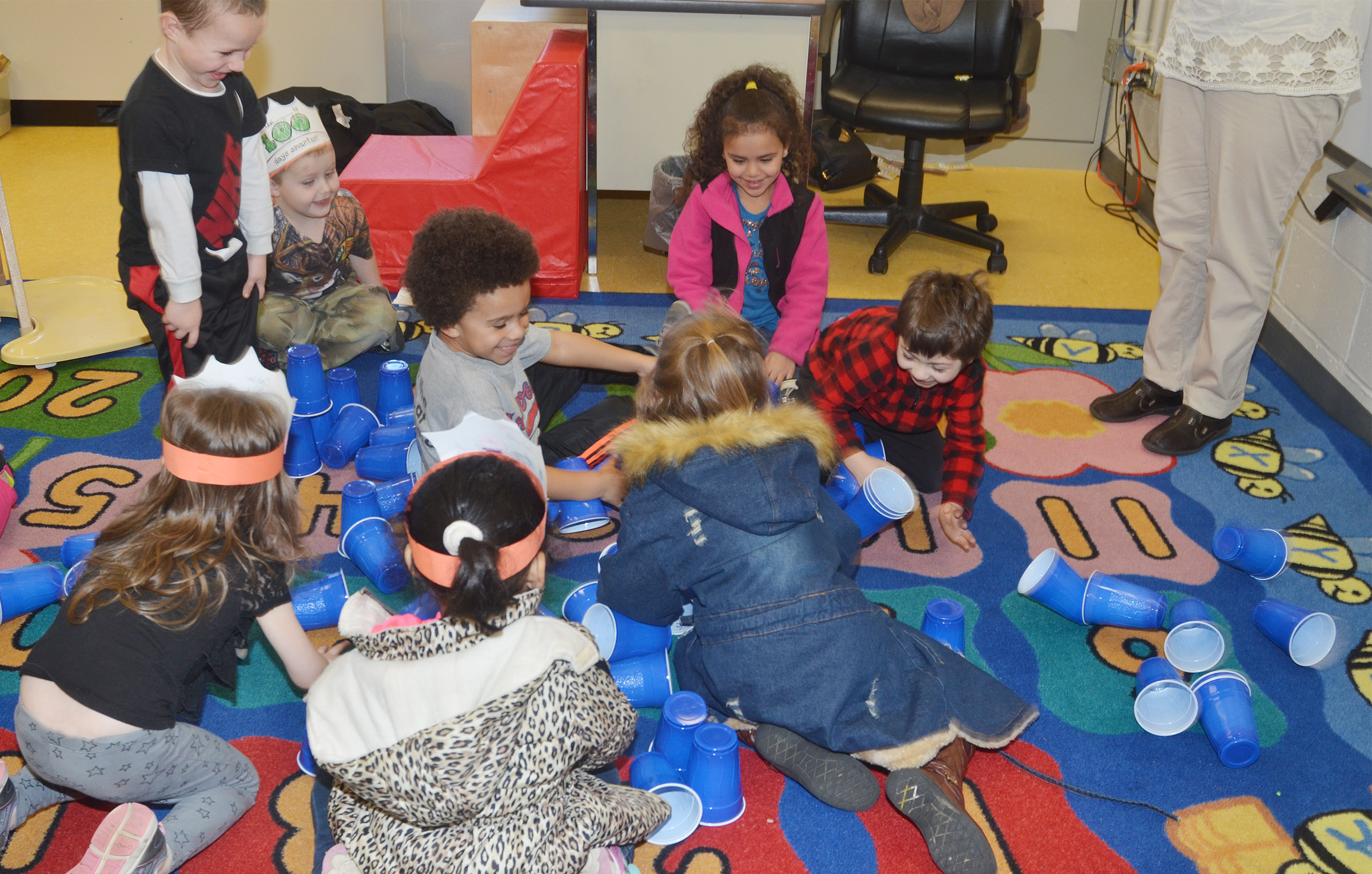 CES preschool students knock all the cups down after they stacked 100 of them in celebration of the 100th day of school.