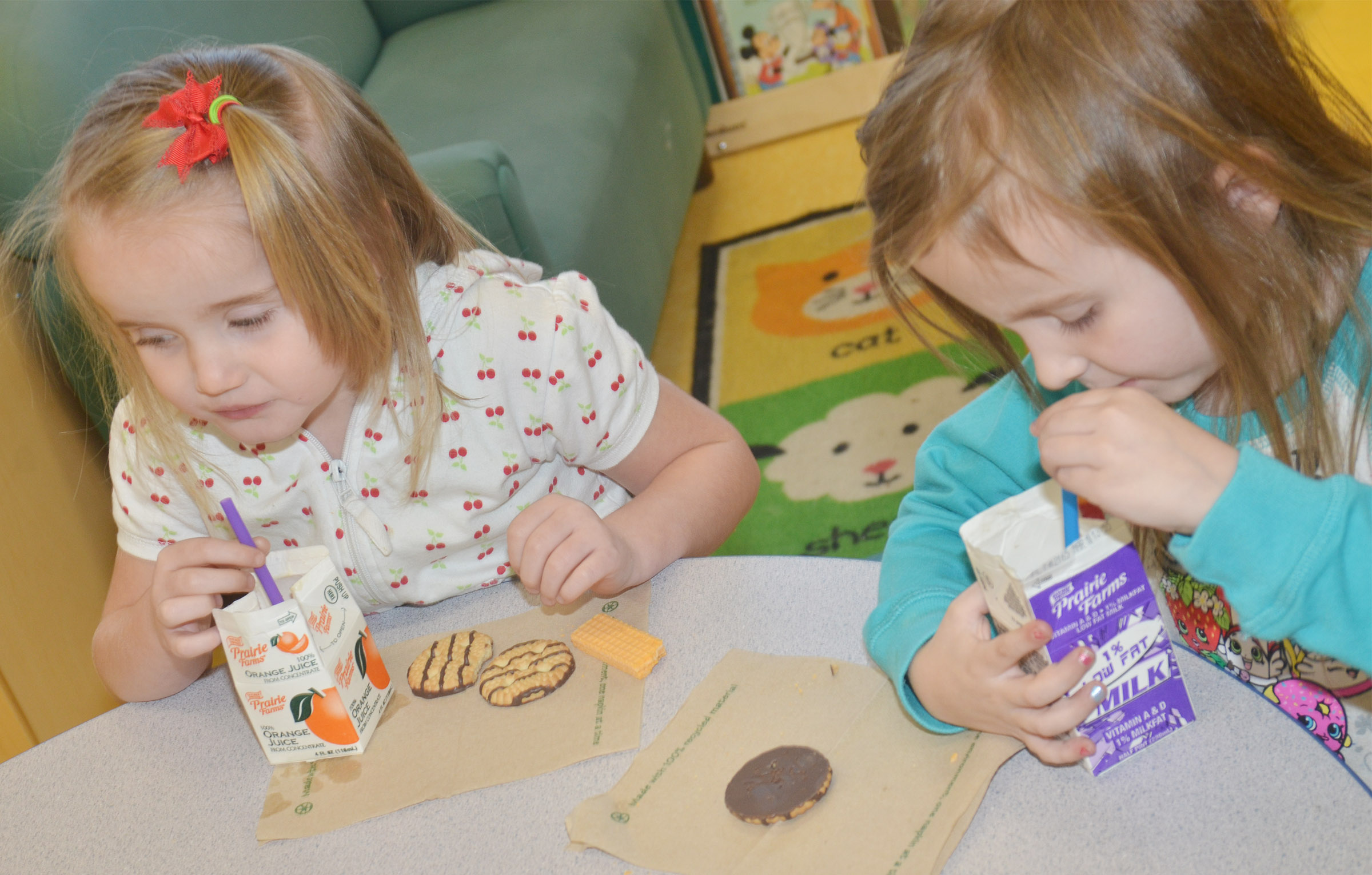 CES preschool students Trinity Dye, at left, and Tabitha Leggett enjoy their special snacks on the 100th day of school.