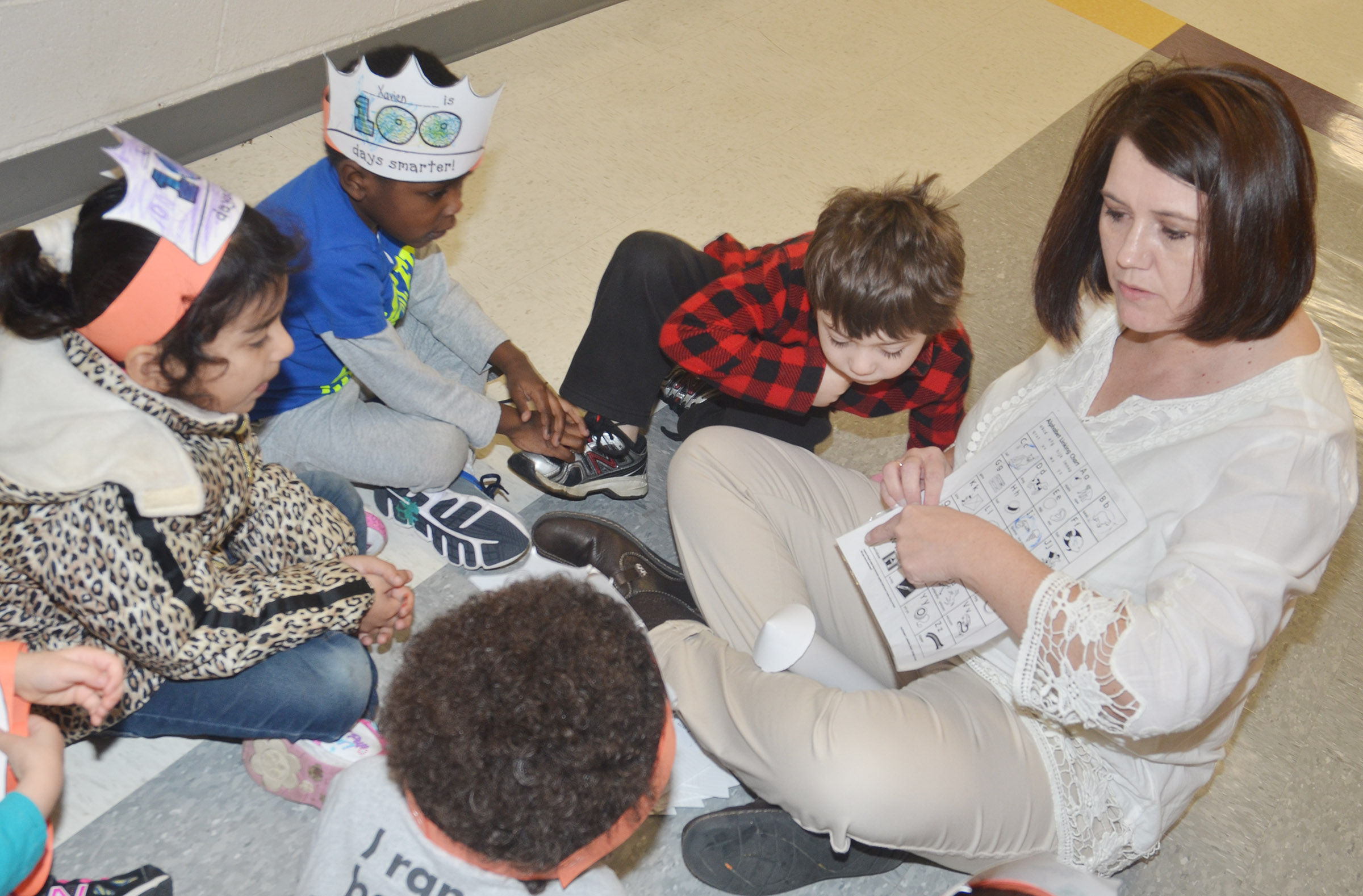 CES preschool teacher Denise Spencer helps students recite the alphabet on the 100th day of school.