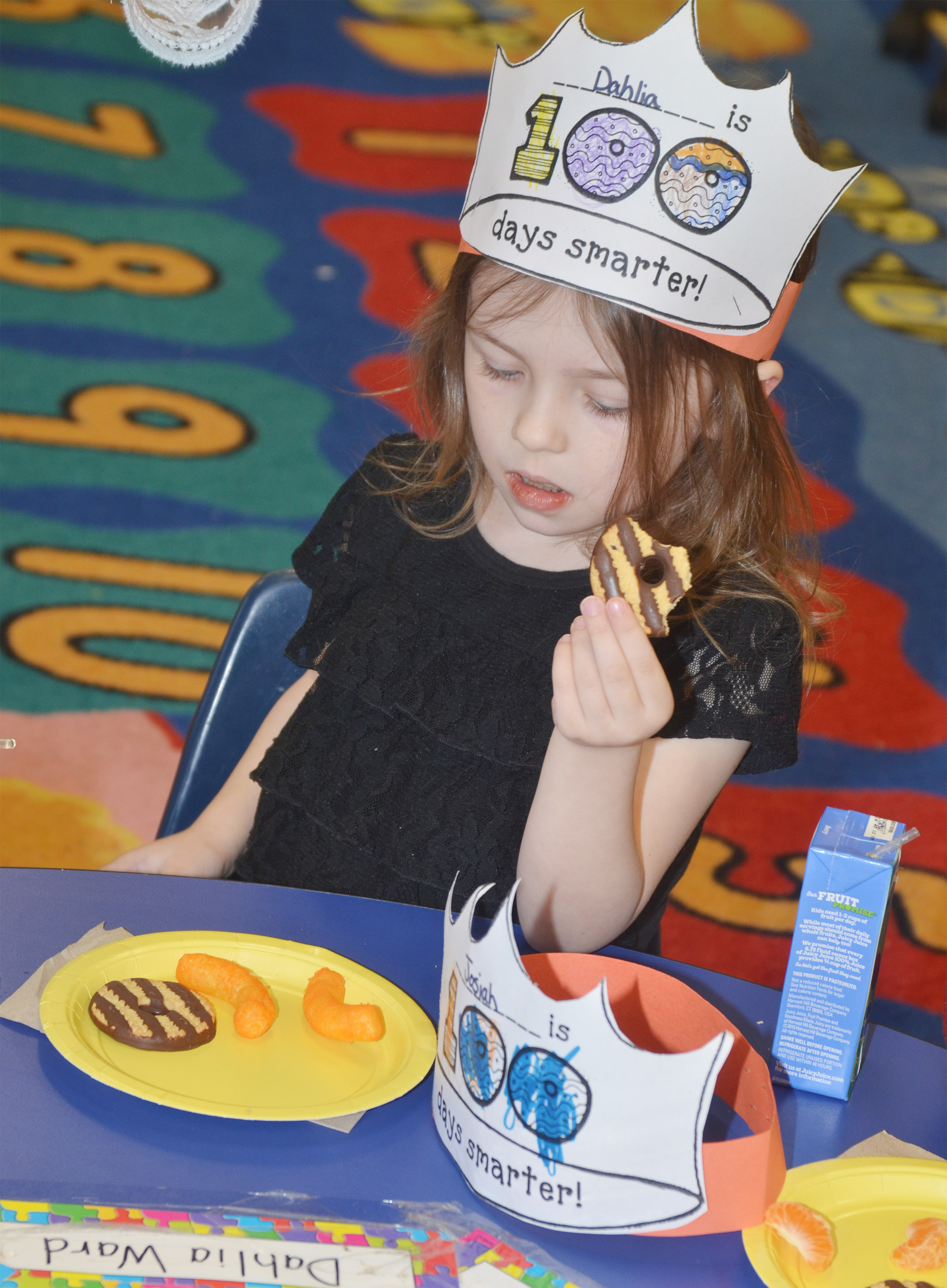 CES preschool student Dahlia Ward eats her special snack on the 100th day of school.