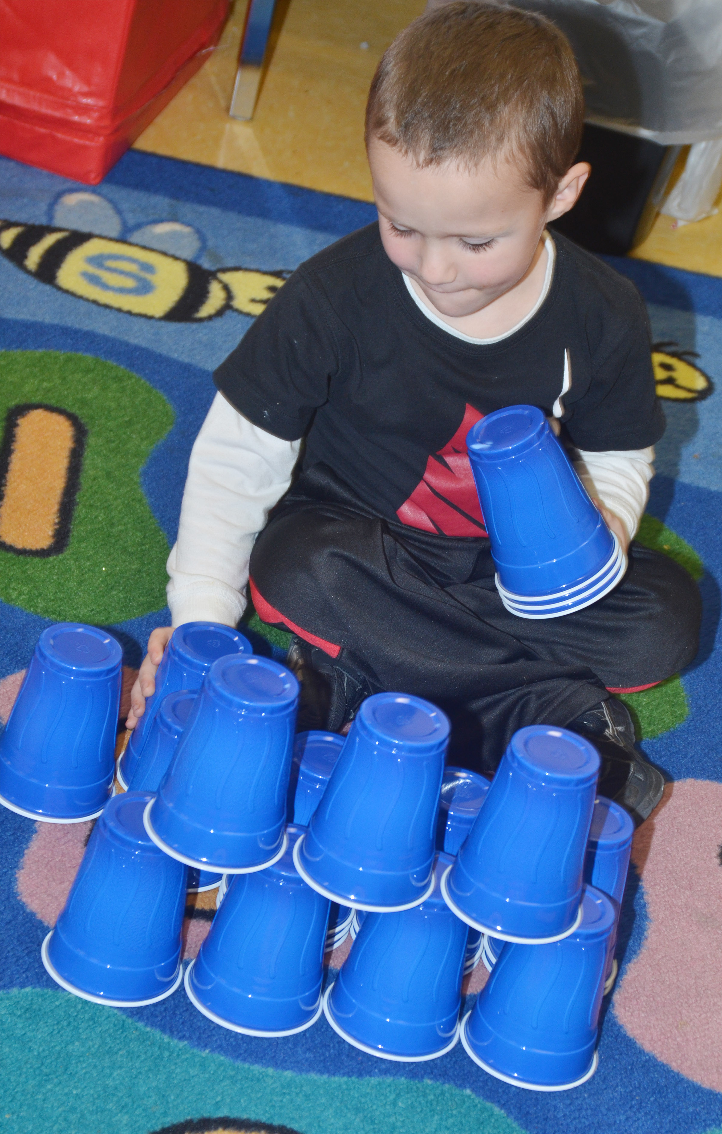 CES preschool student Triton Bradshaw stacks cups on the 100th day of school. His class stacked a total of 100 cups.