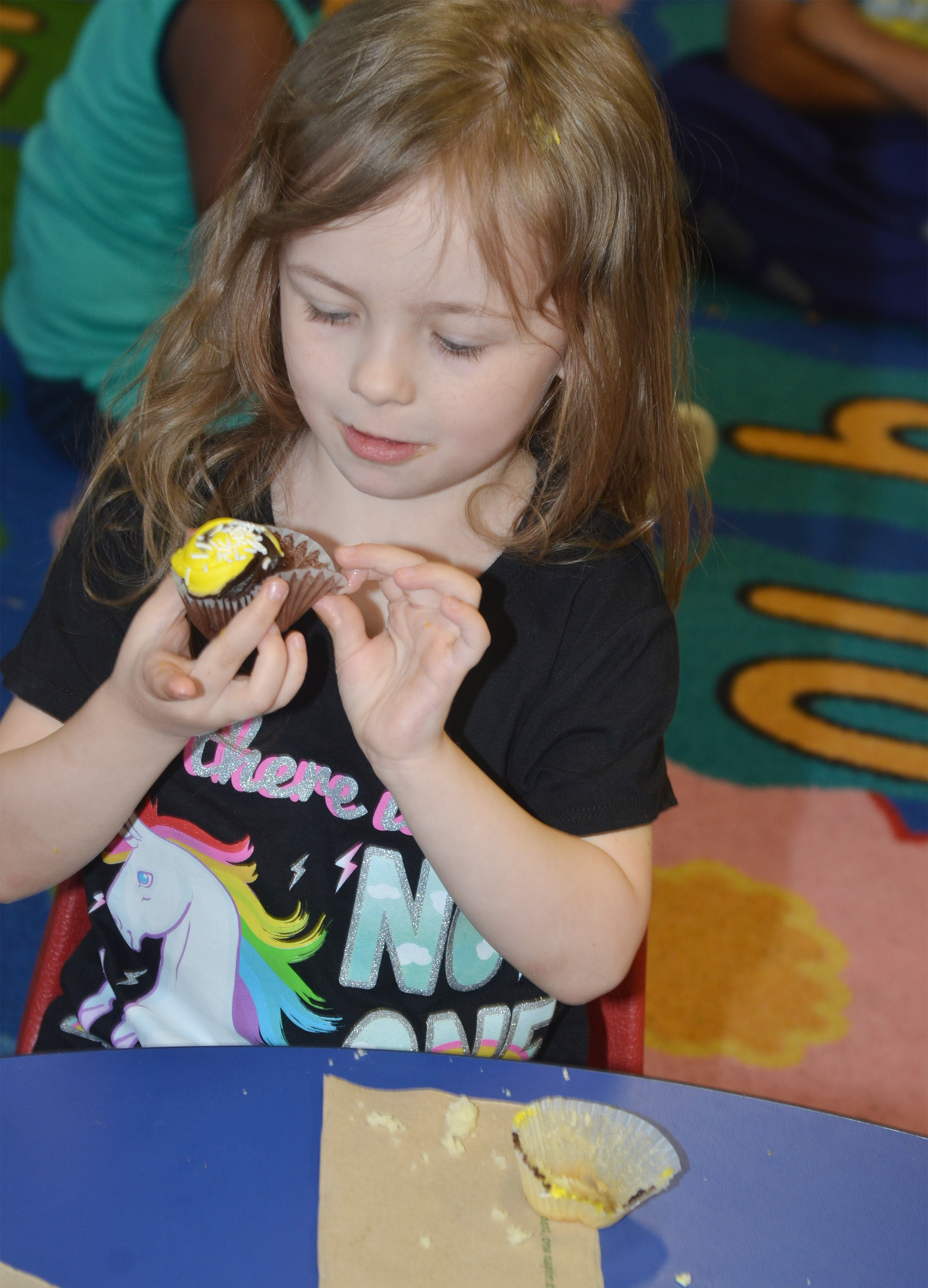 CES preschool student Dahlia Ward enjoys a birthday cupcake.