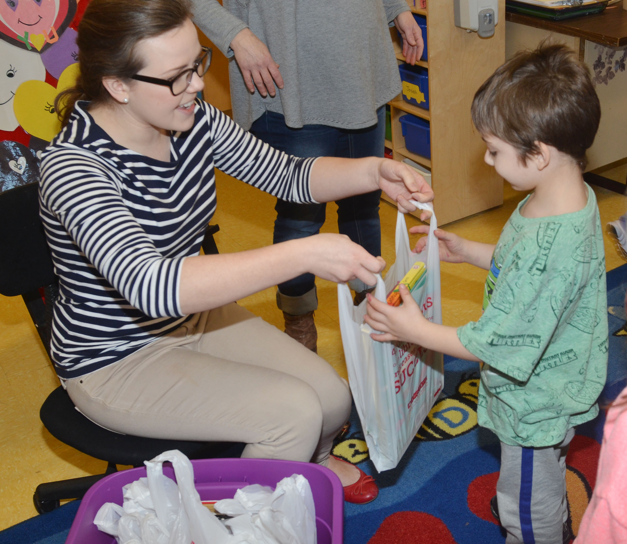 Campbellsville University education student Amanda Hamilton passes out books to CES preschool student Josiah Dean.