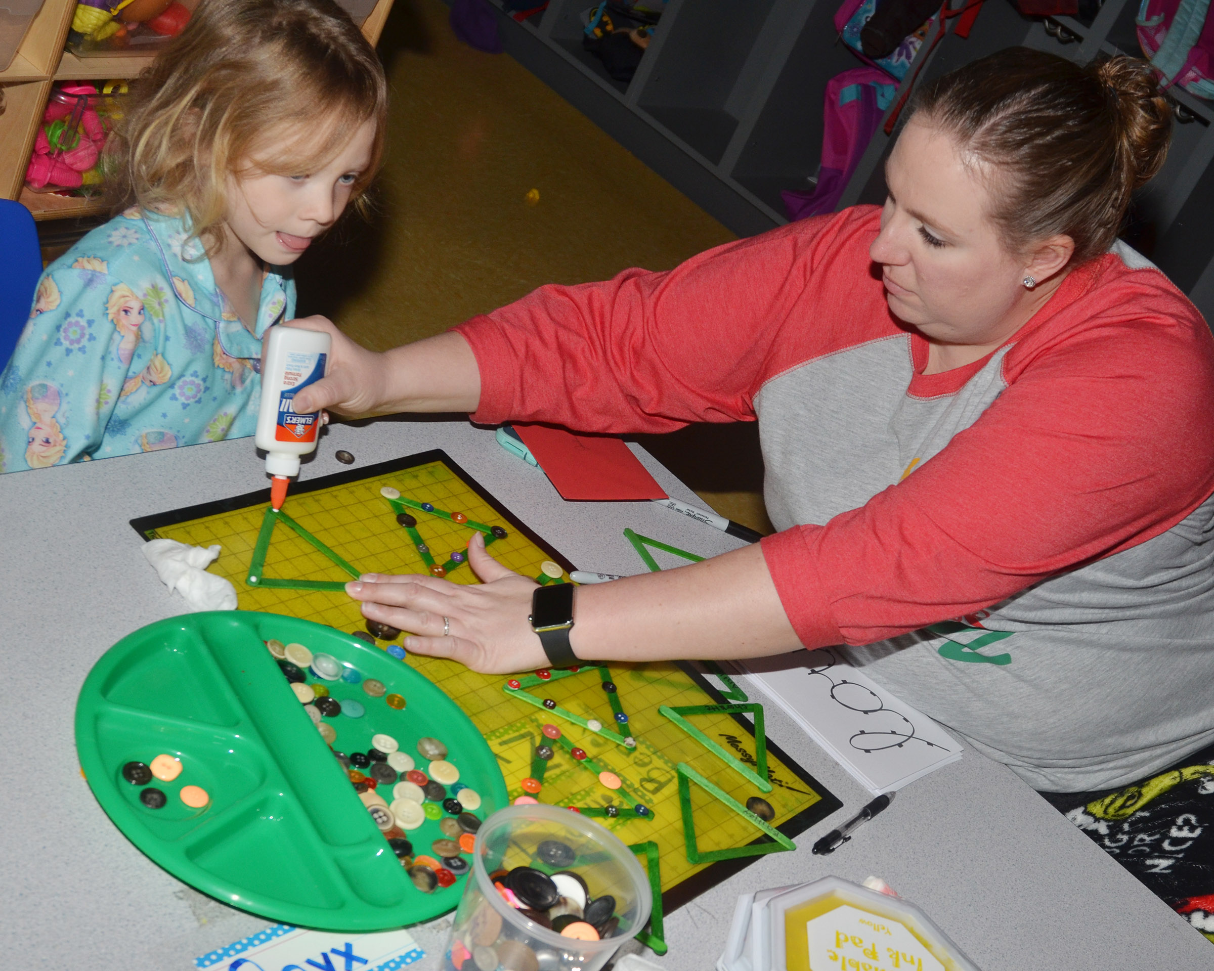 CES preschool teacher Julie Shelton helps Aubree Hall make a Christmas picture frame.
