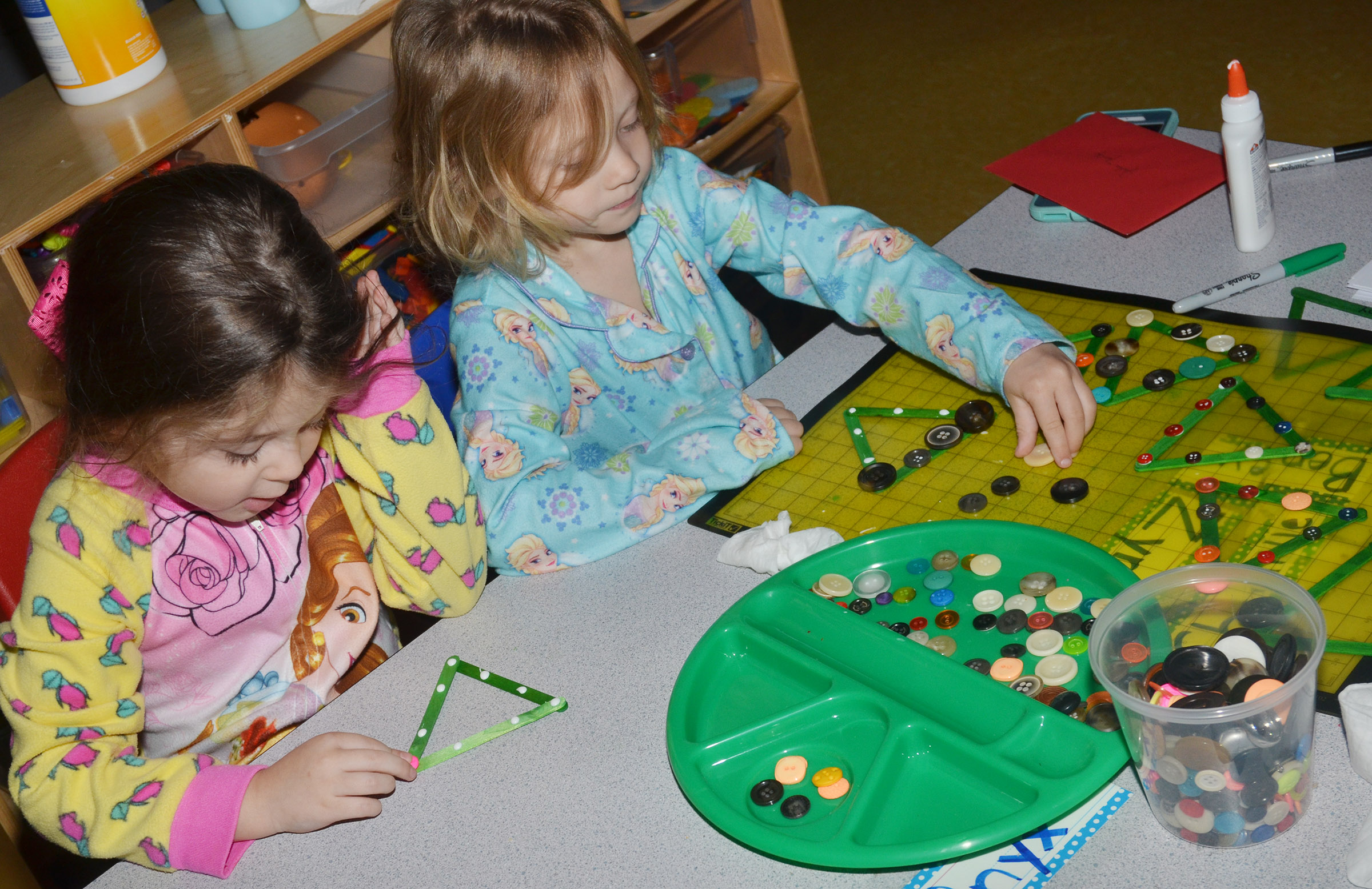 CES preschool students Mila Moss, at left, and Aubree Hall make Christmas picture frames.