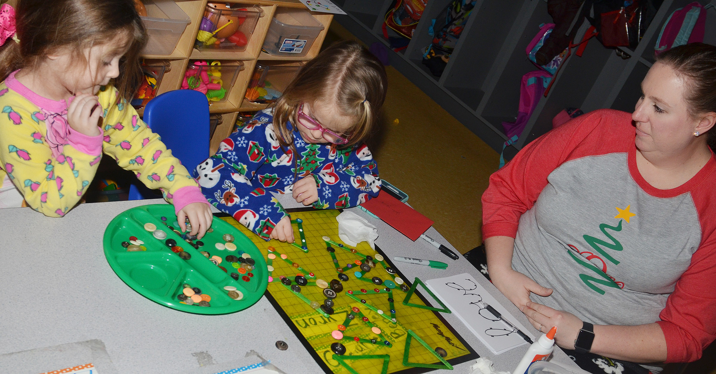 CES preschool teacher Julie Shelton helps Mila Moss, at left, and Charlotte Coots make Christmas picture frames.