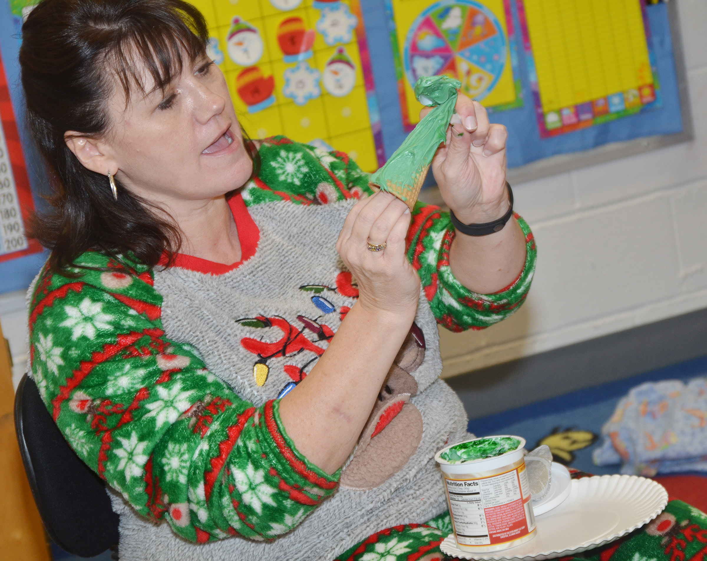 CES preschool teacher Denise Spencer shows students how to decorate their own edible Christmas trees.
