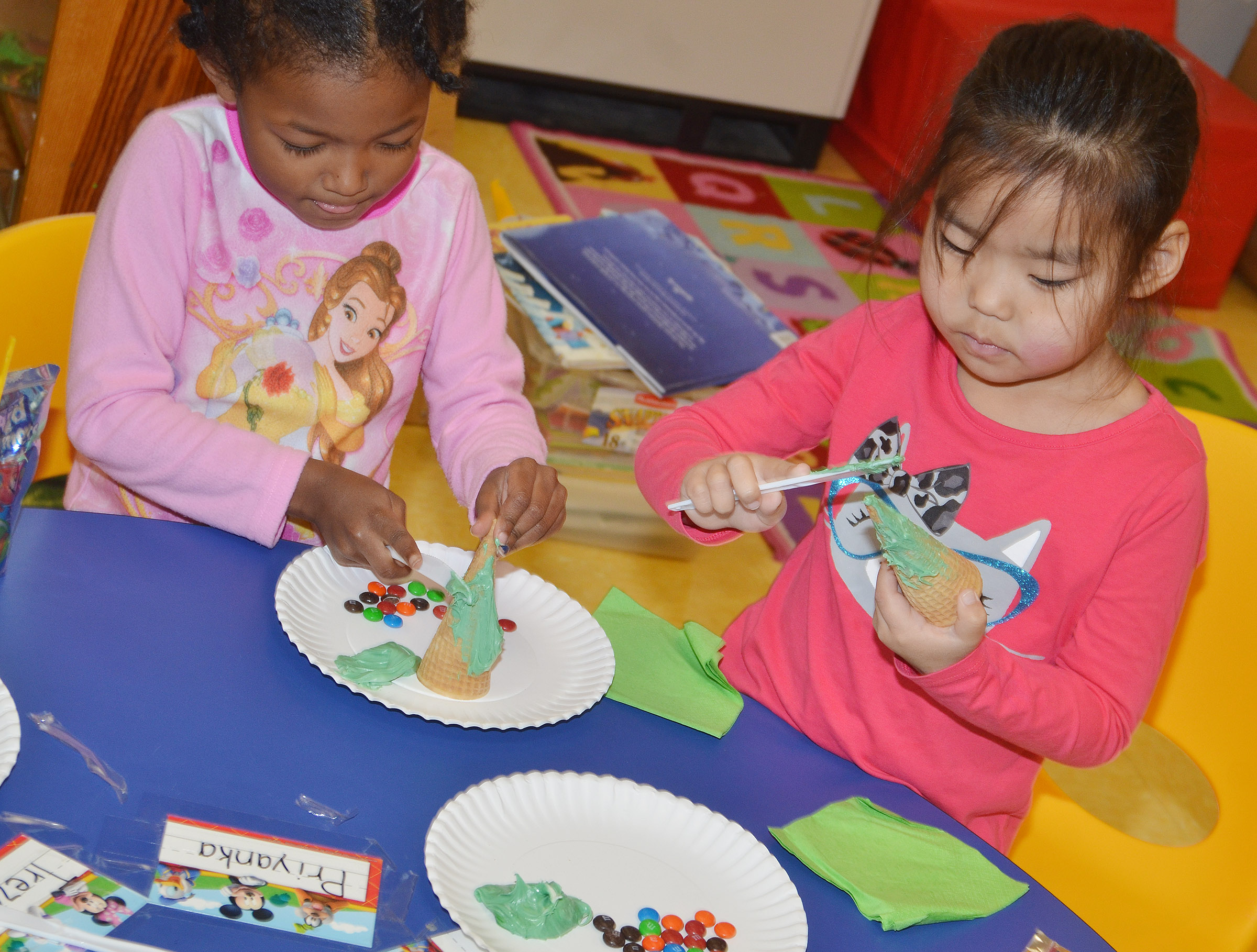 CES preschool students Priyanka Flores, at left, and Marla Bat decorate their edible Christmas trees.