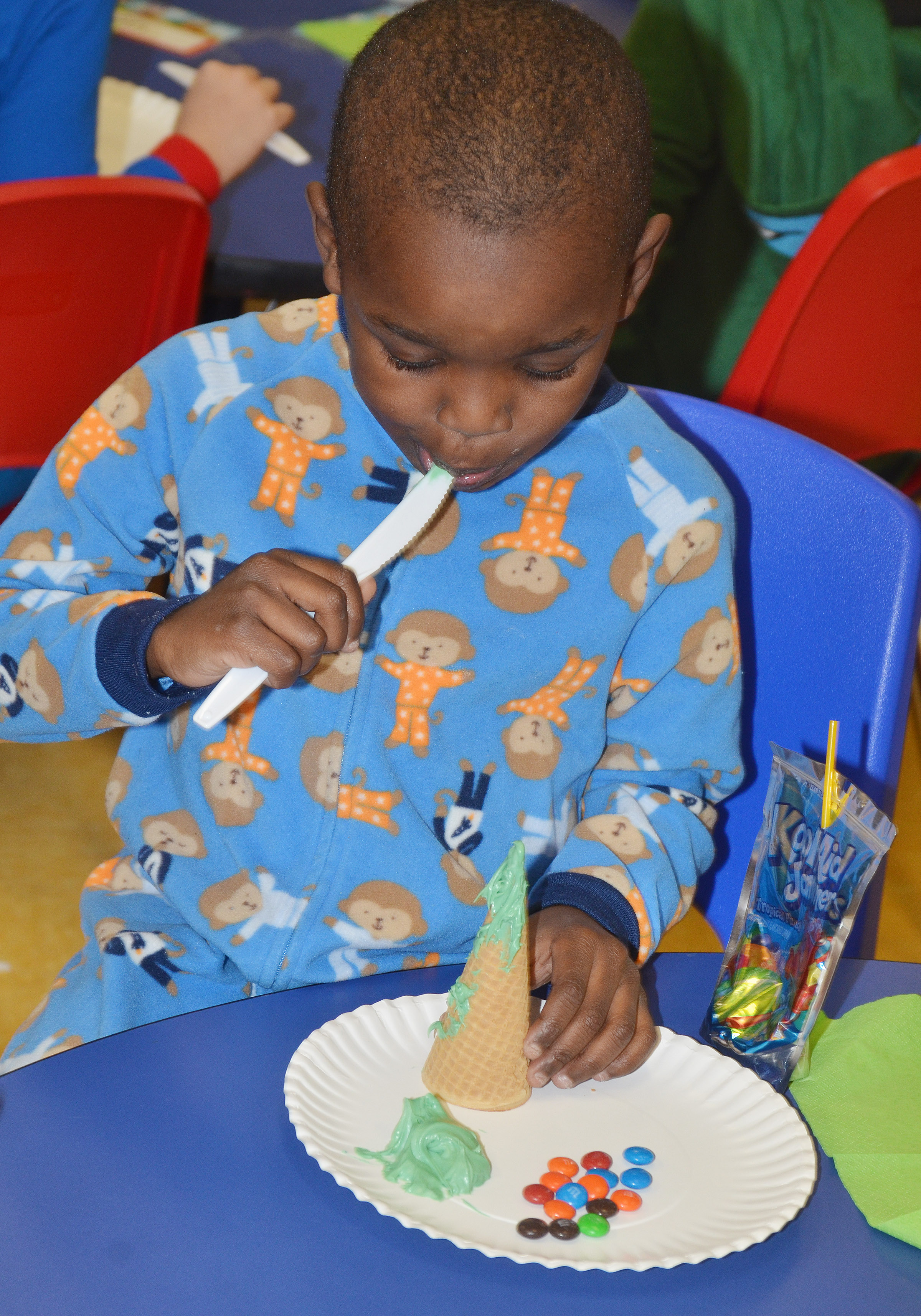 CES preschool student Xavien Smith licks icing as he makes his edible Christmas tree.